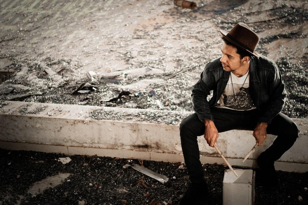 man in black coat sitting on concrete fence holding drumstick