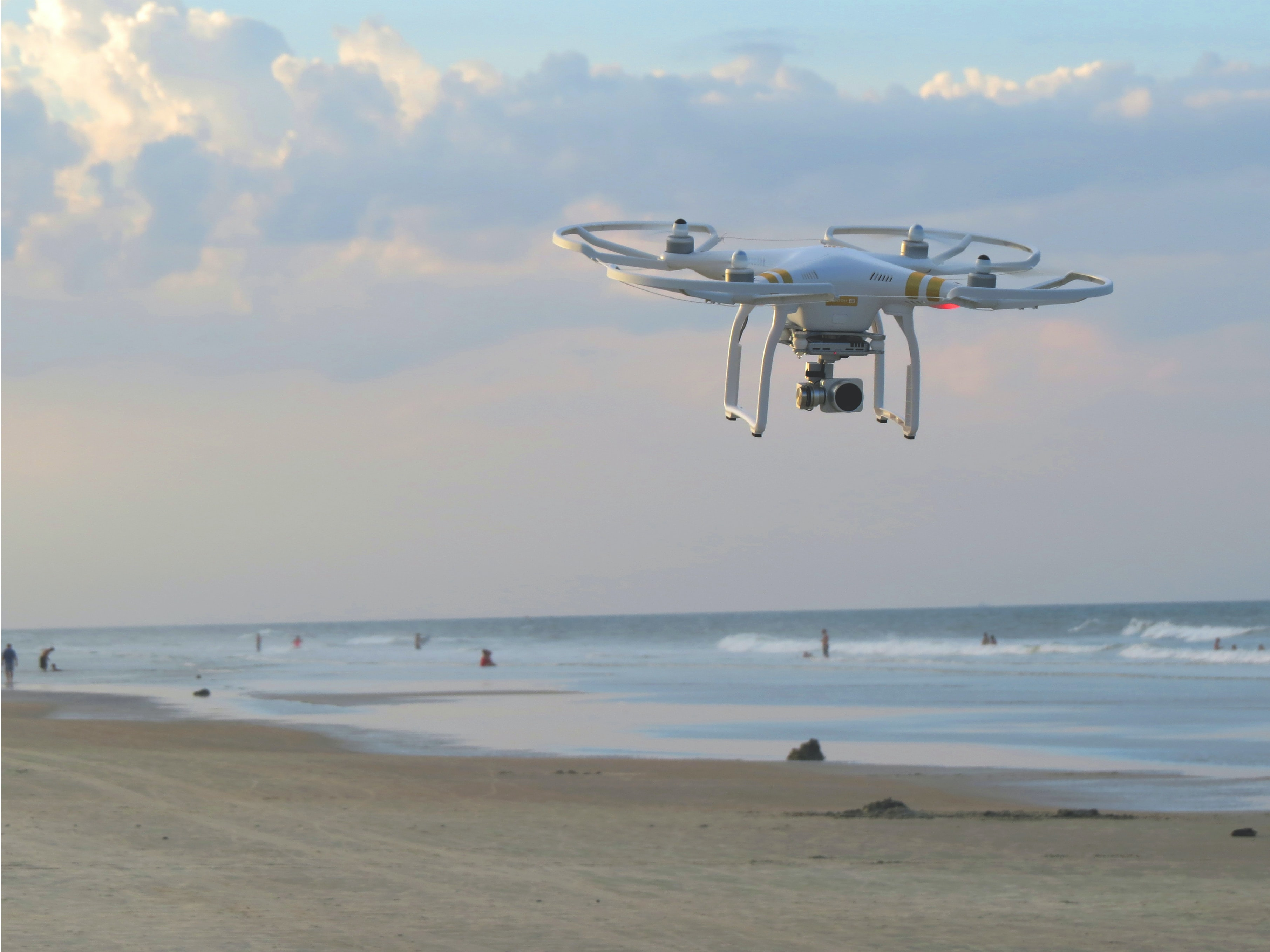 DJI 3 drone flying above the sand beach at New Smyrna Beach
