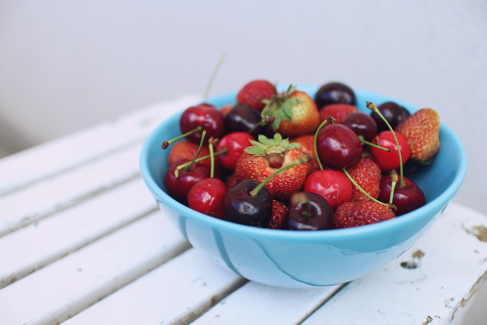 focus photography of strawberries and cherries on blue bowl
