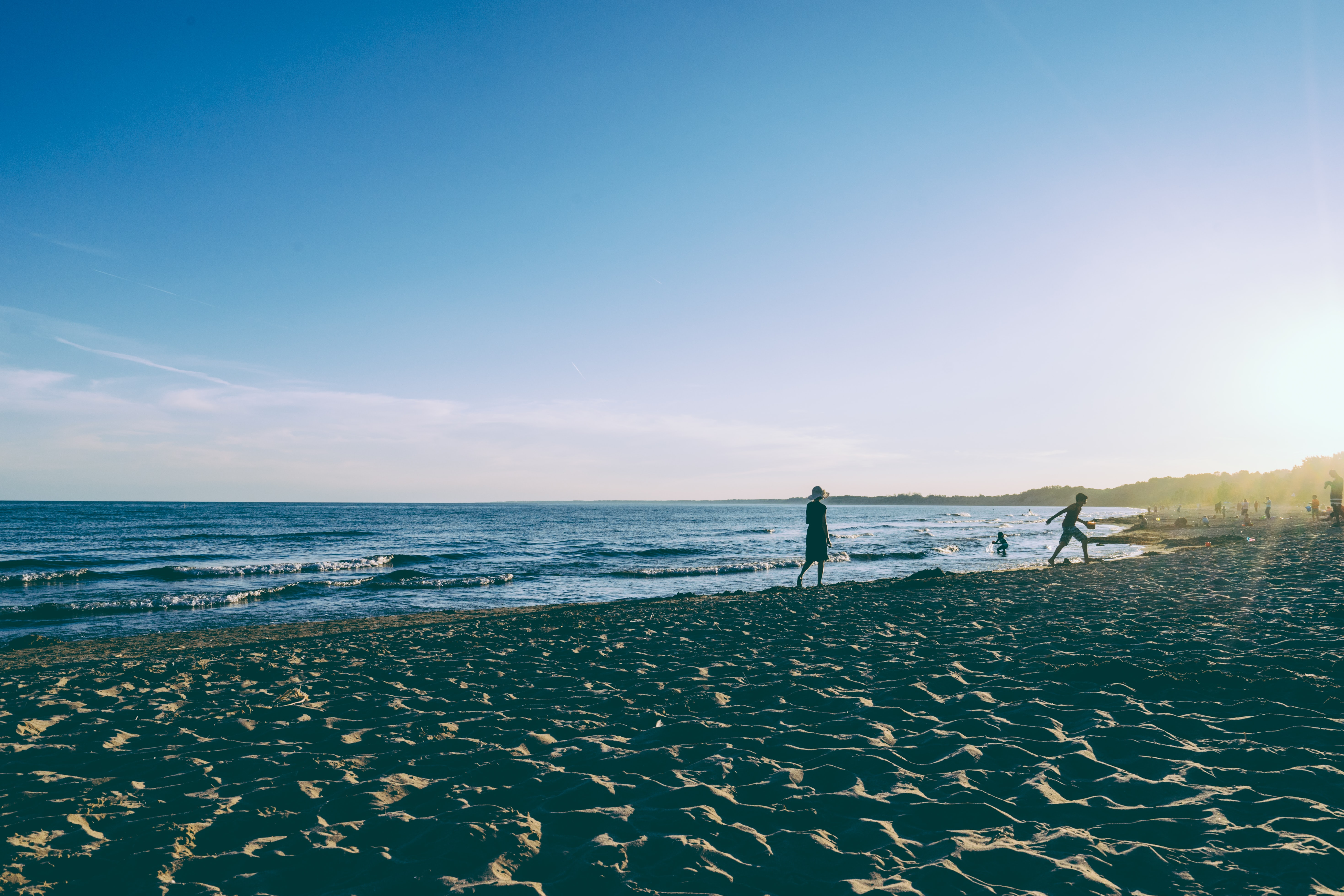 two person walking on seashore during daytime