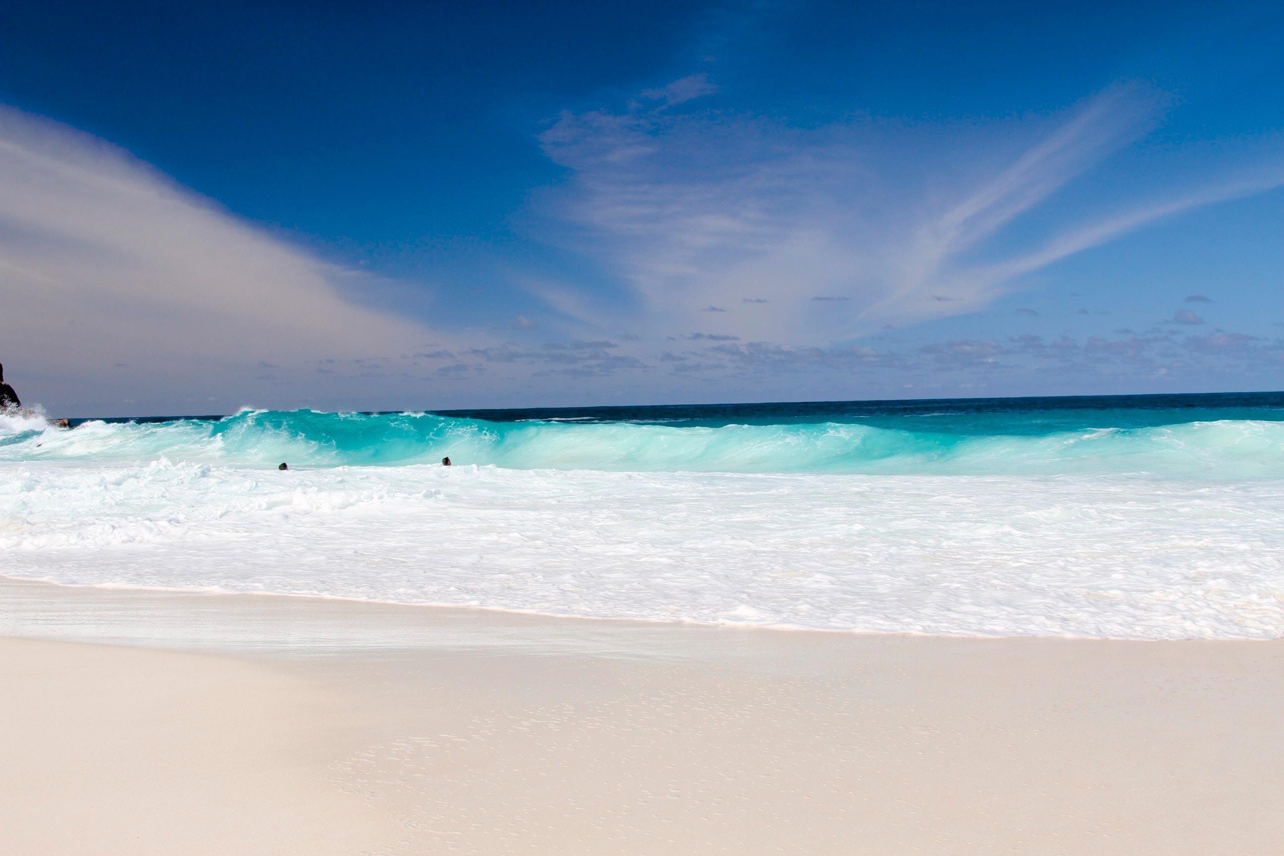 Blue ocean waves splashing on a tropical sand beach at Seychelles