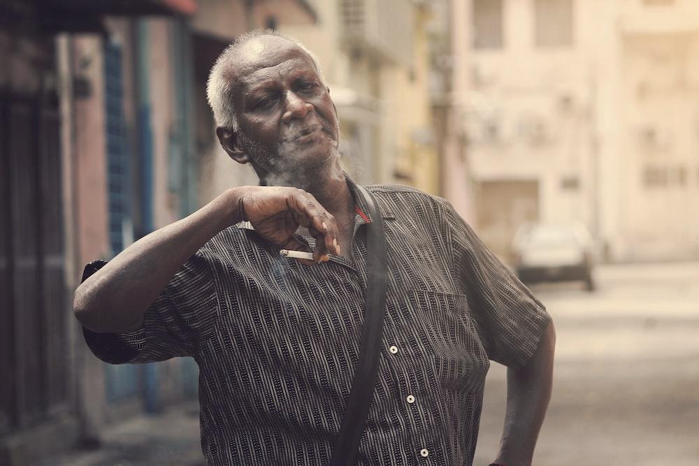 man holding cigarette during daytime