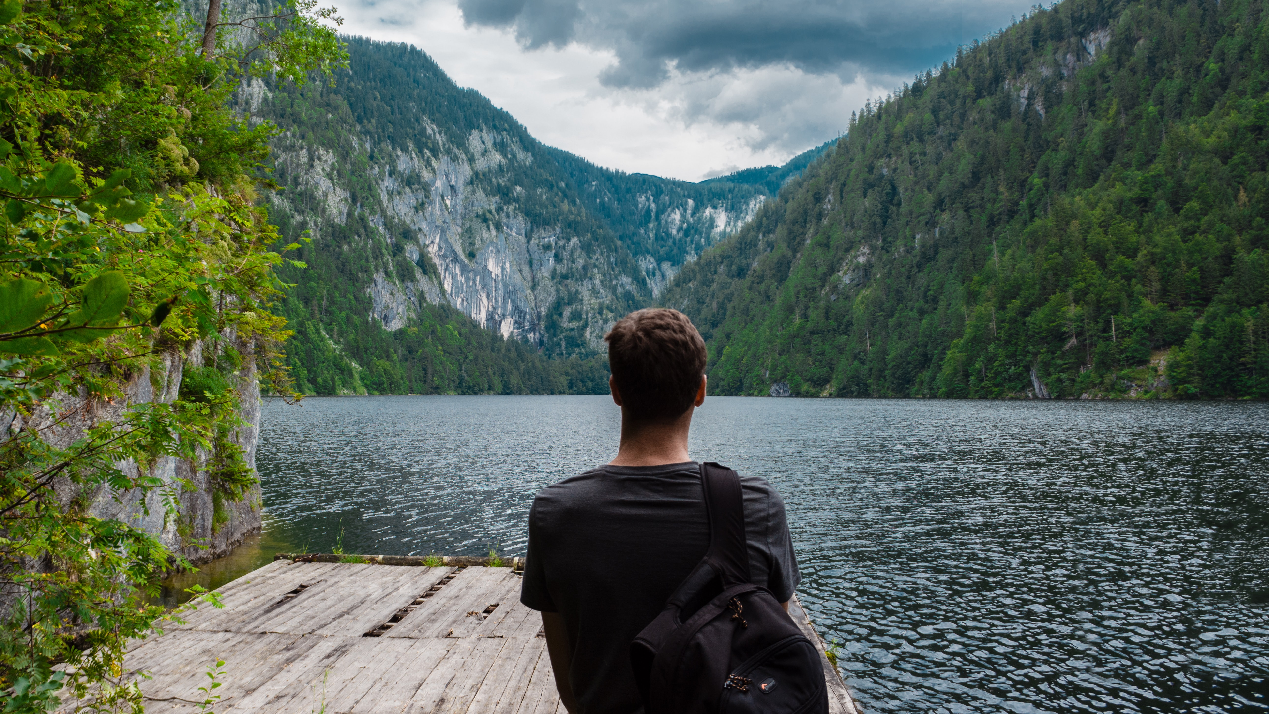 A man with a backpack on a wooden platform on a mountain lake in Austria