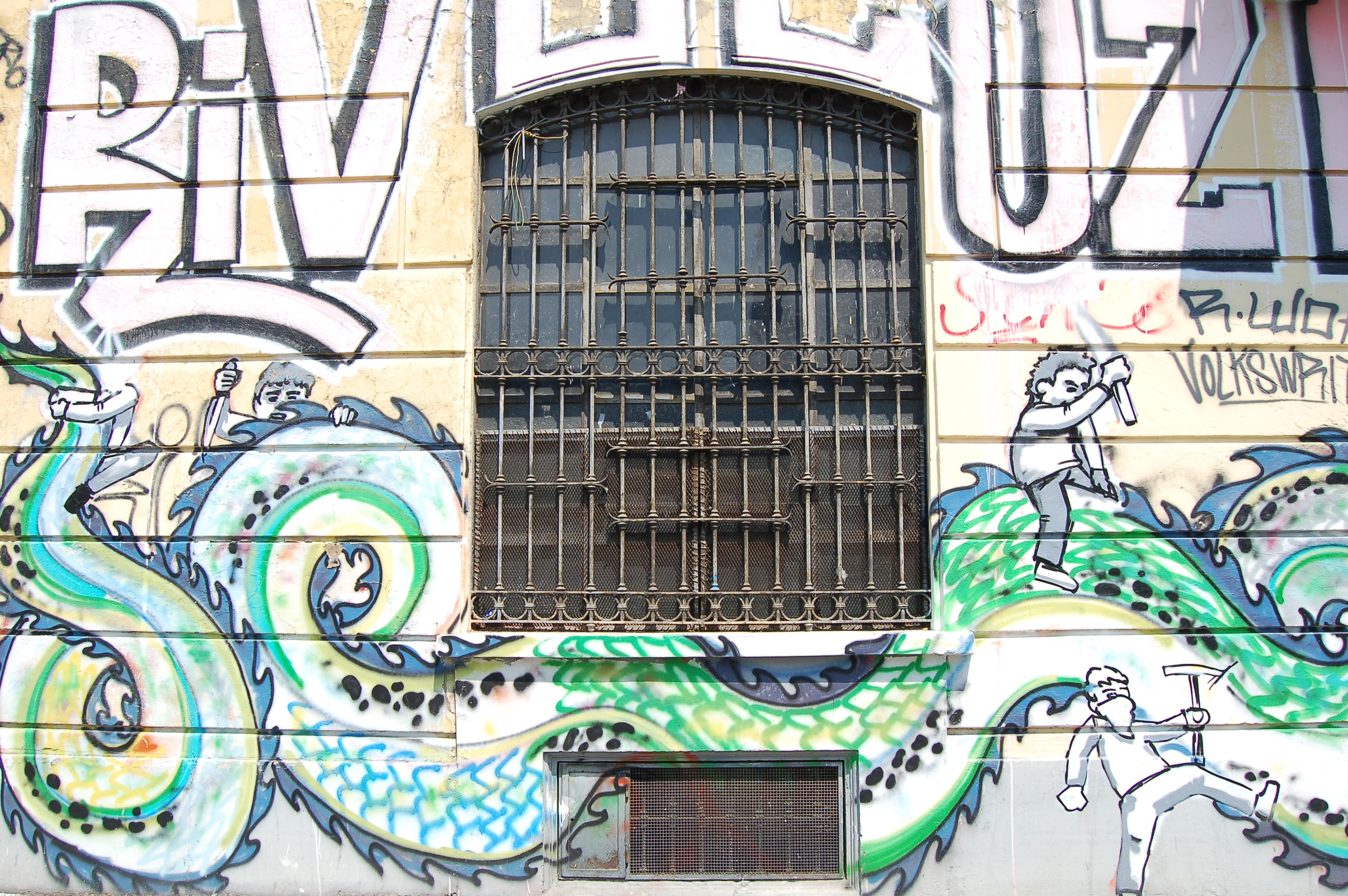 Text and snake dragon graffiti on building wall with barred windows
