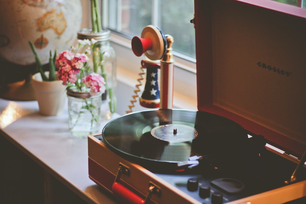 brown Crosley turntable beside candlestick telephone