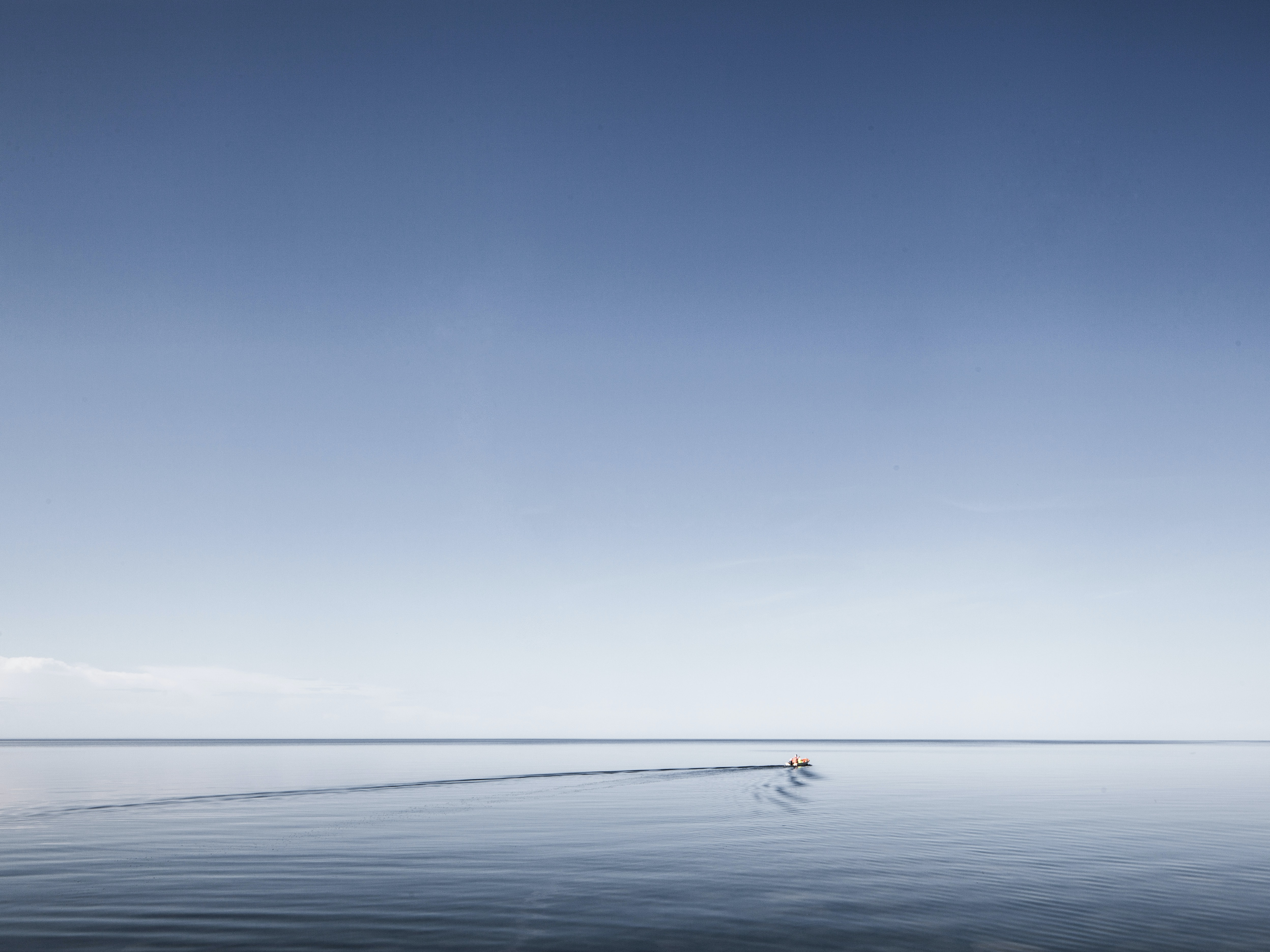 A small boat leaves ripples on the smooth surface of water stretching to the horizon