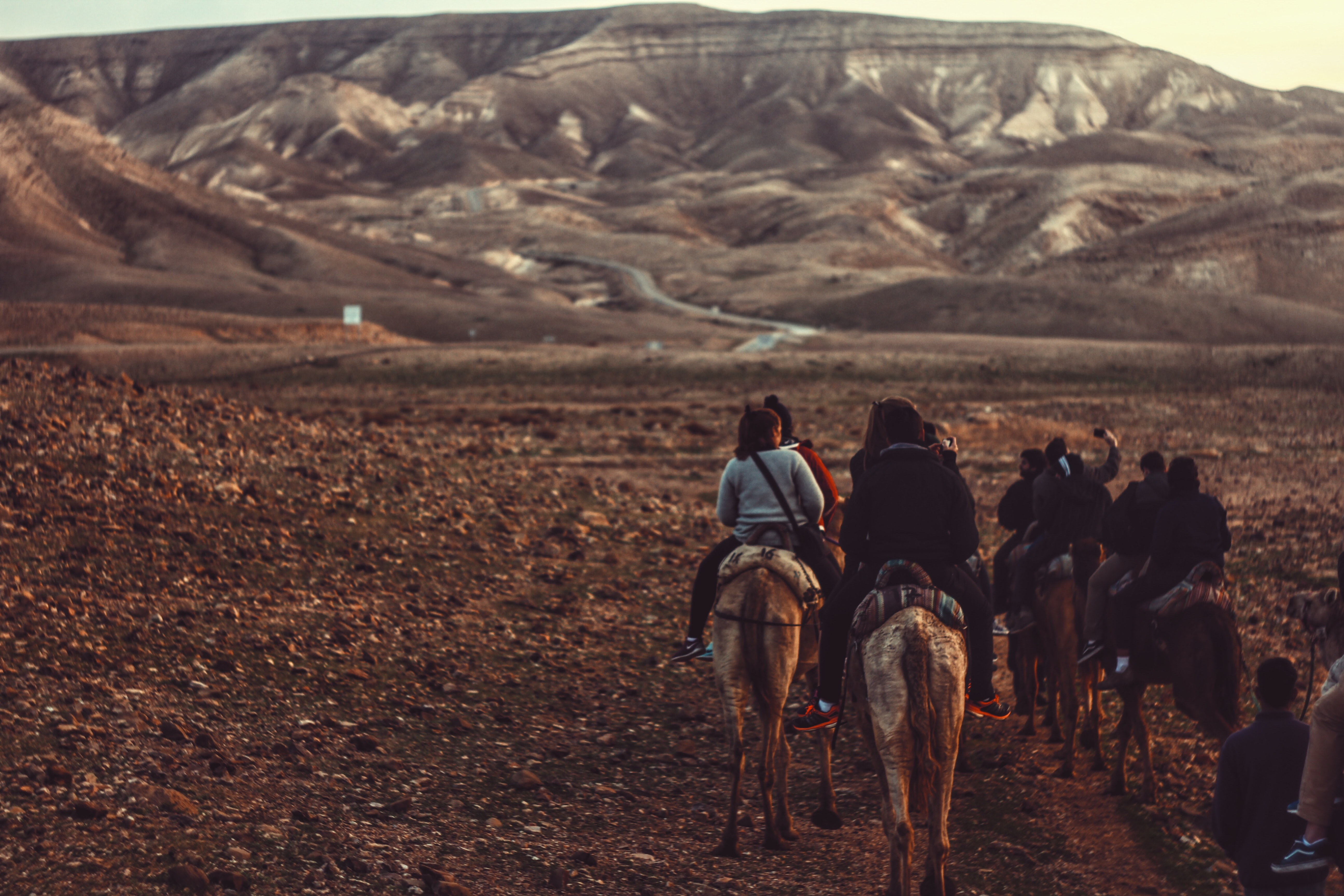A group of people riding horses through dry wilderness towards a mountain range