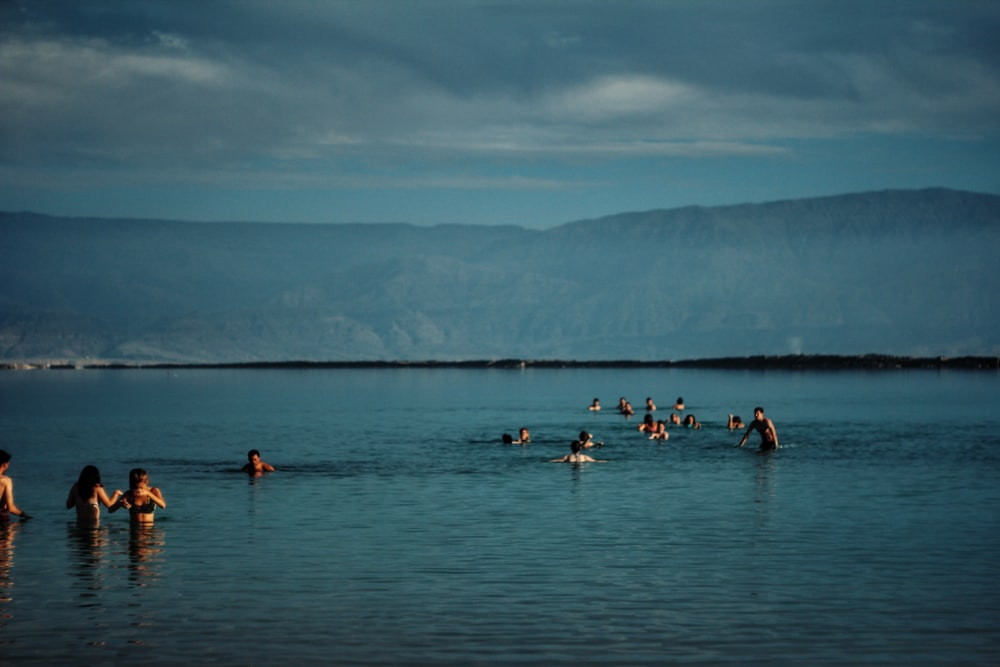 group of people in body of water near green mountain