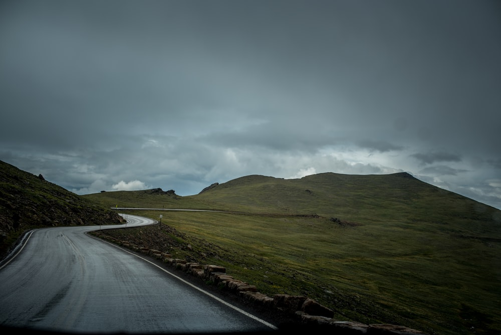 photo of gray concrete road between green mountain and green grass field under cloudy sky