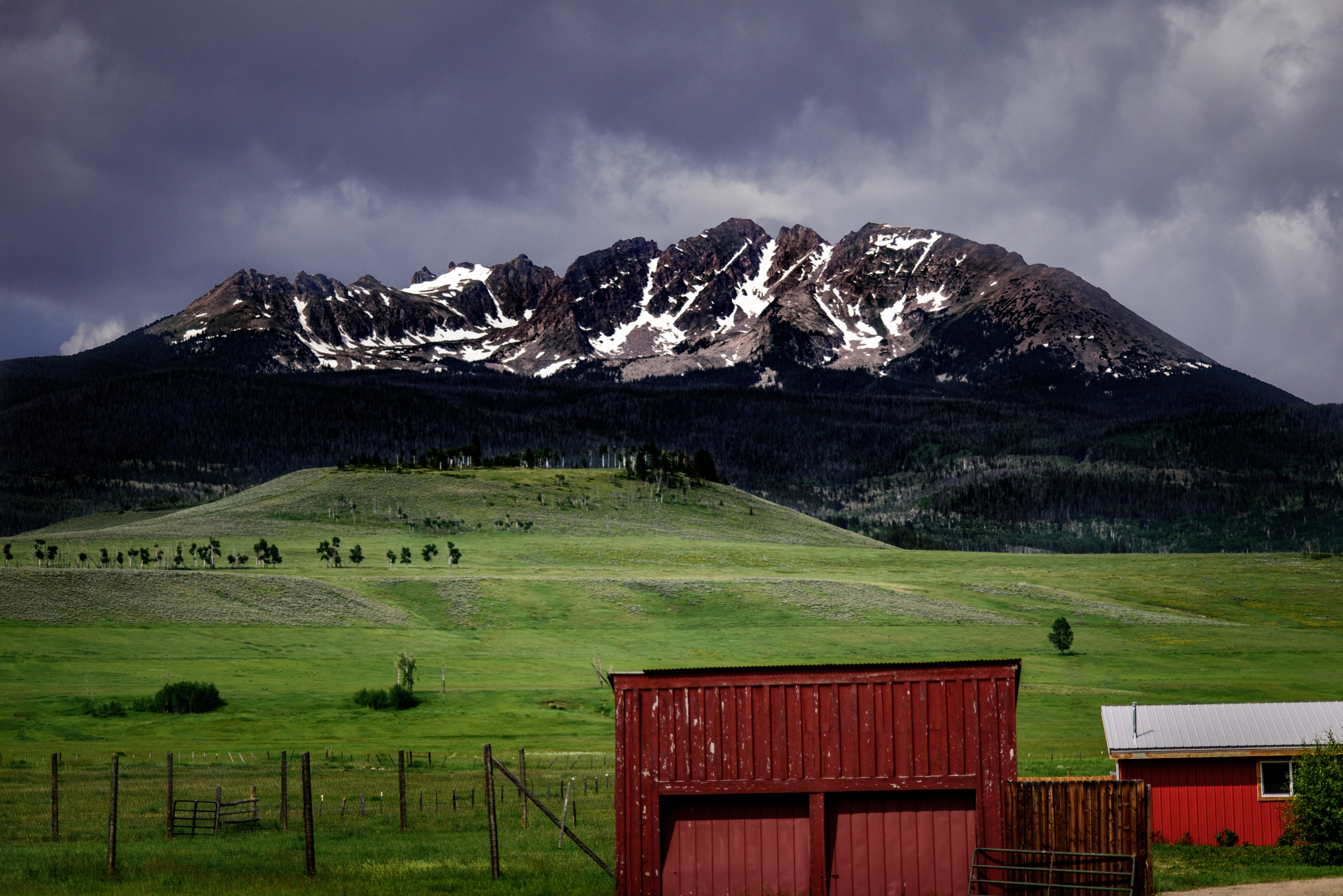 landscape photo of green grass field and mountain