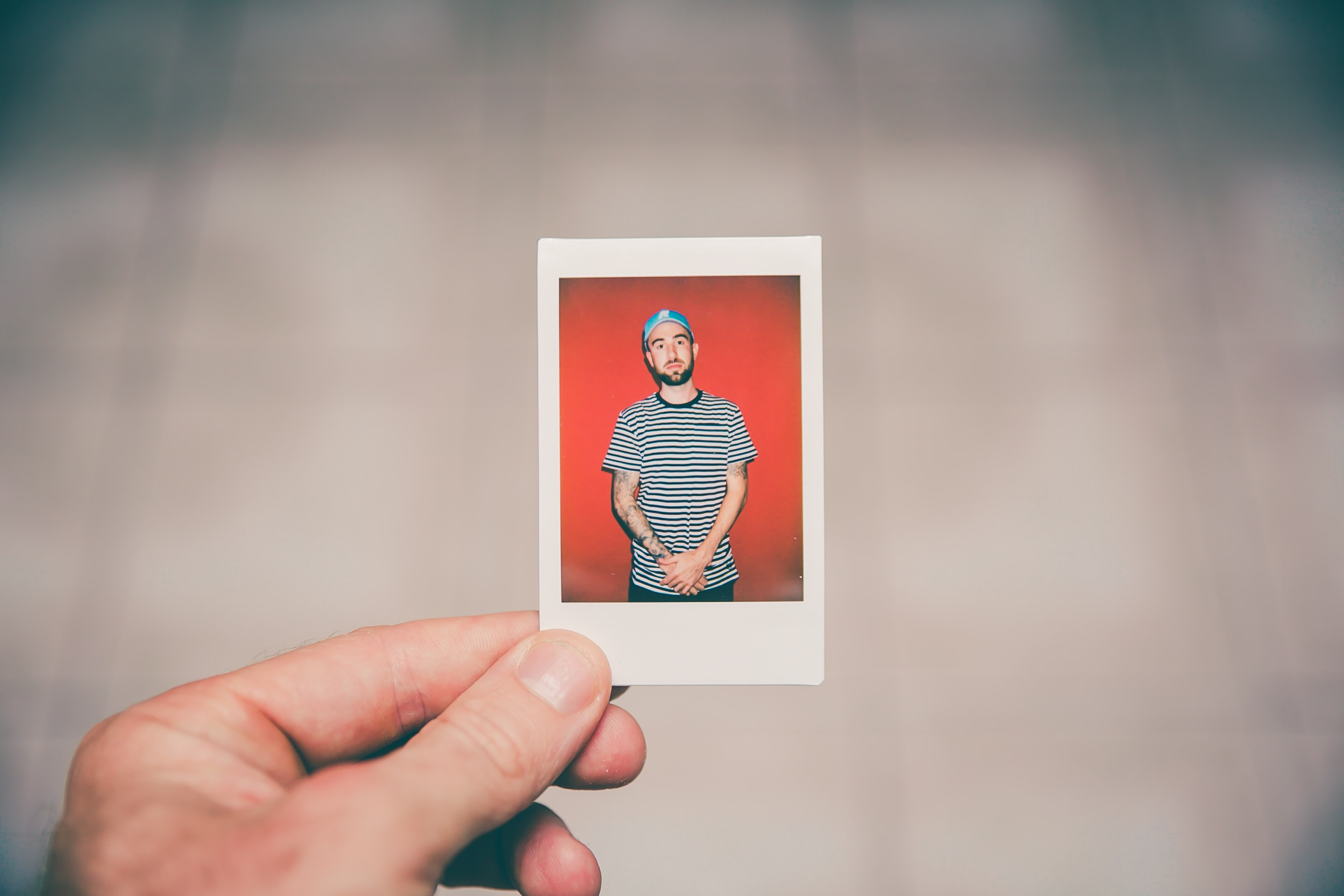 Hand holding a photograph of a man in a striped shirt with tattoos wearing a baseball cap