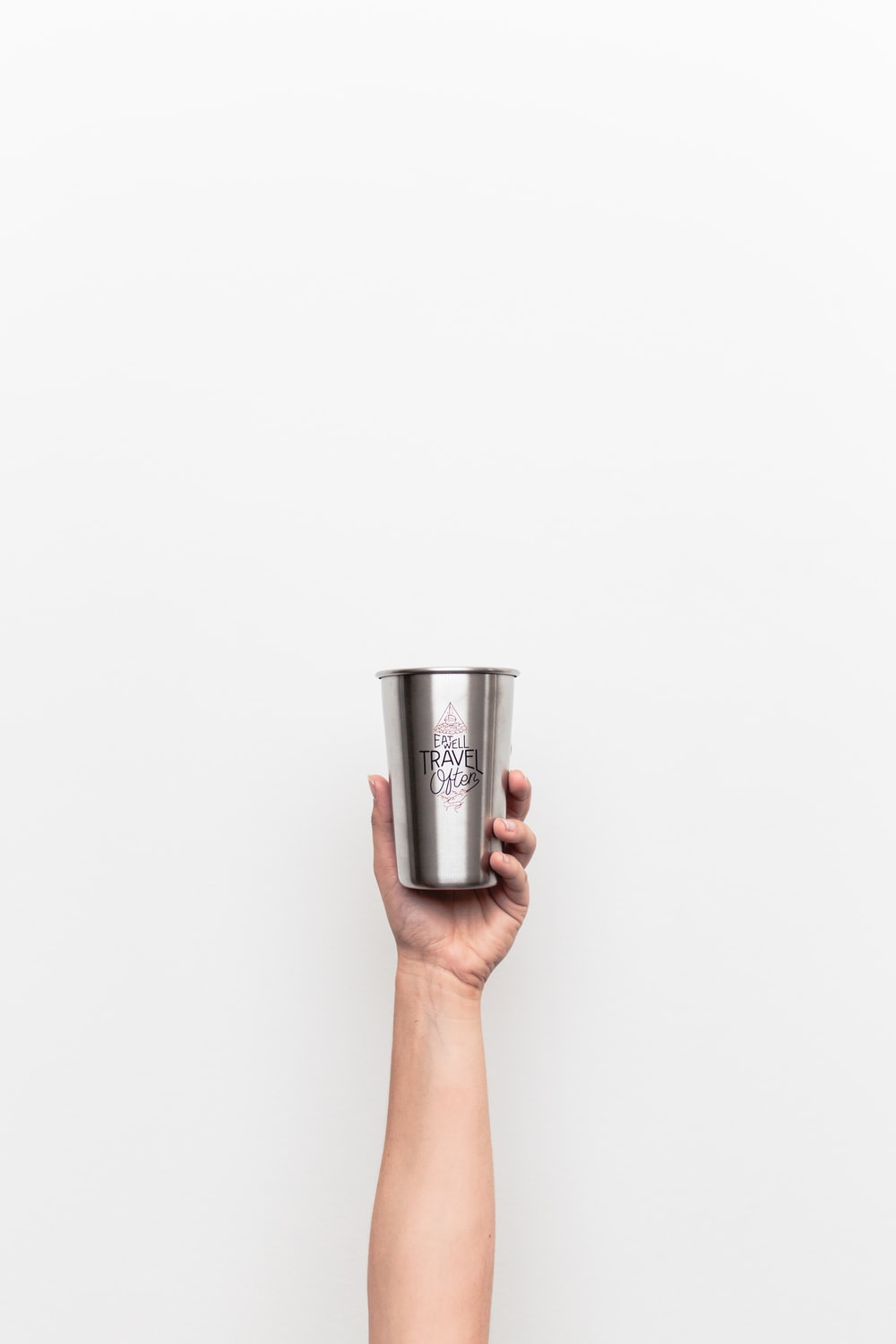 person holding gray stainless steel drinking cup