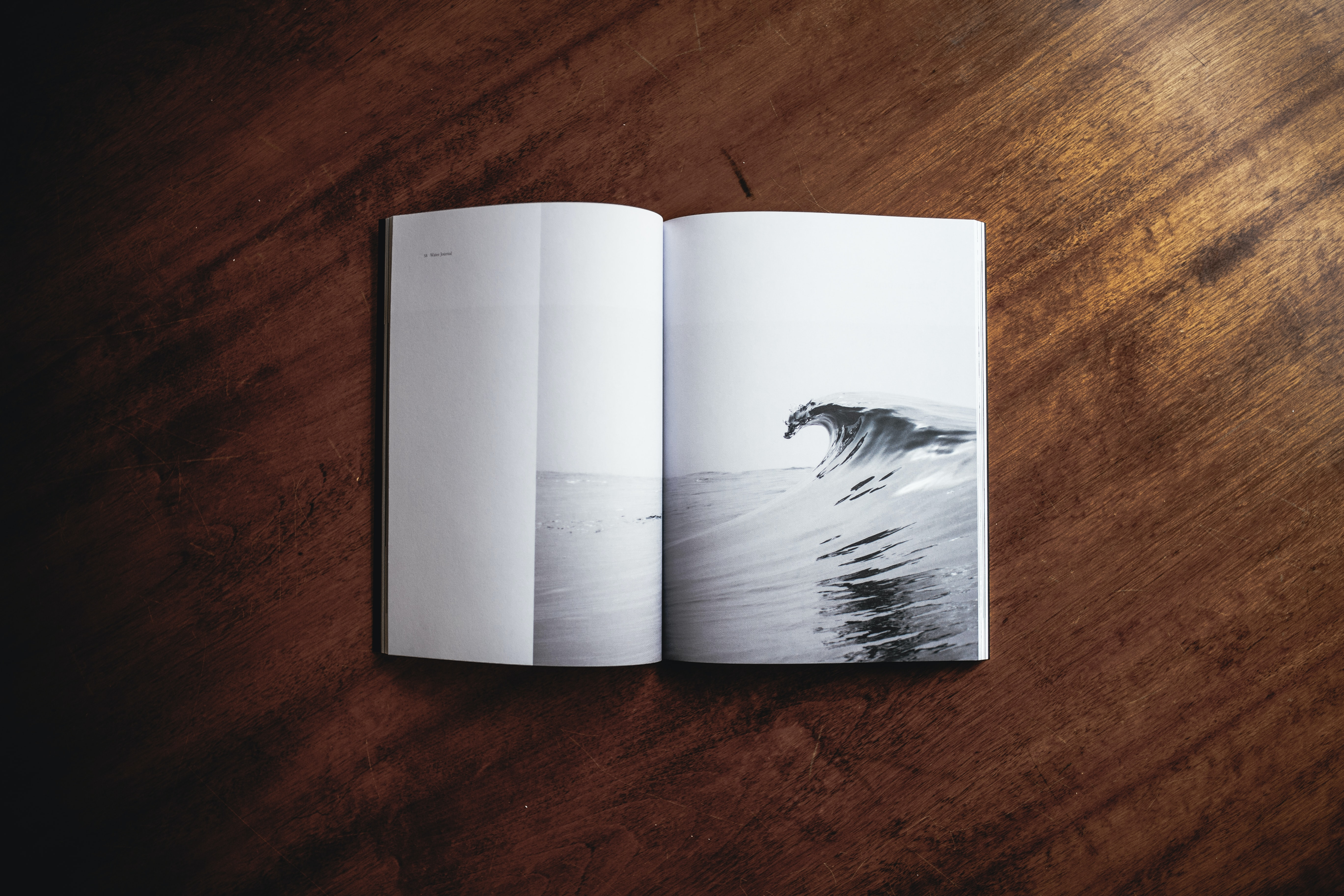 An open book with a photograph of a sea wave on its pages
