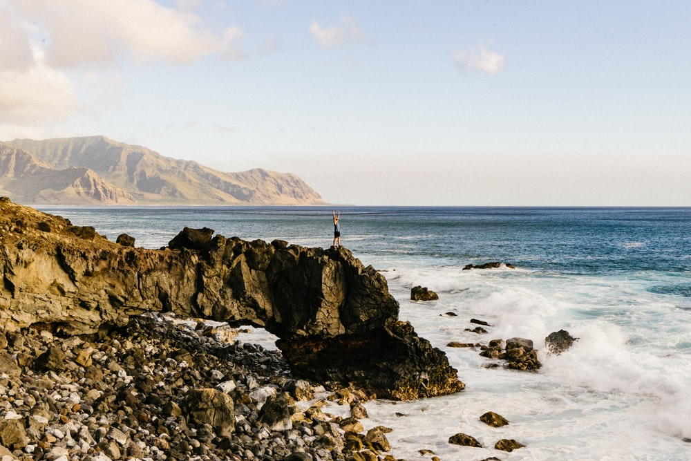 A person standing on the edge of a cliff by the sea with their arms outstretched