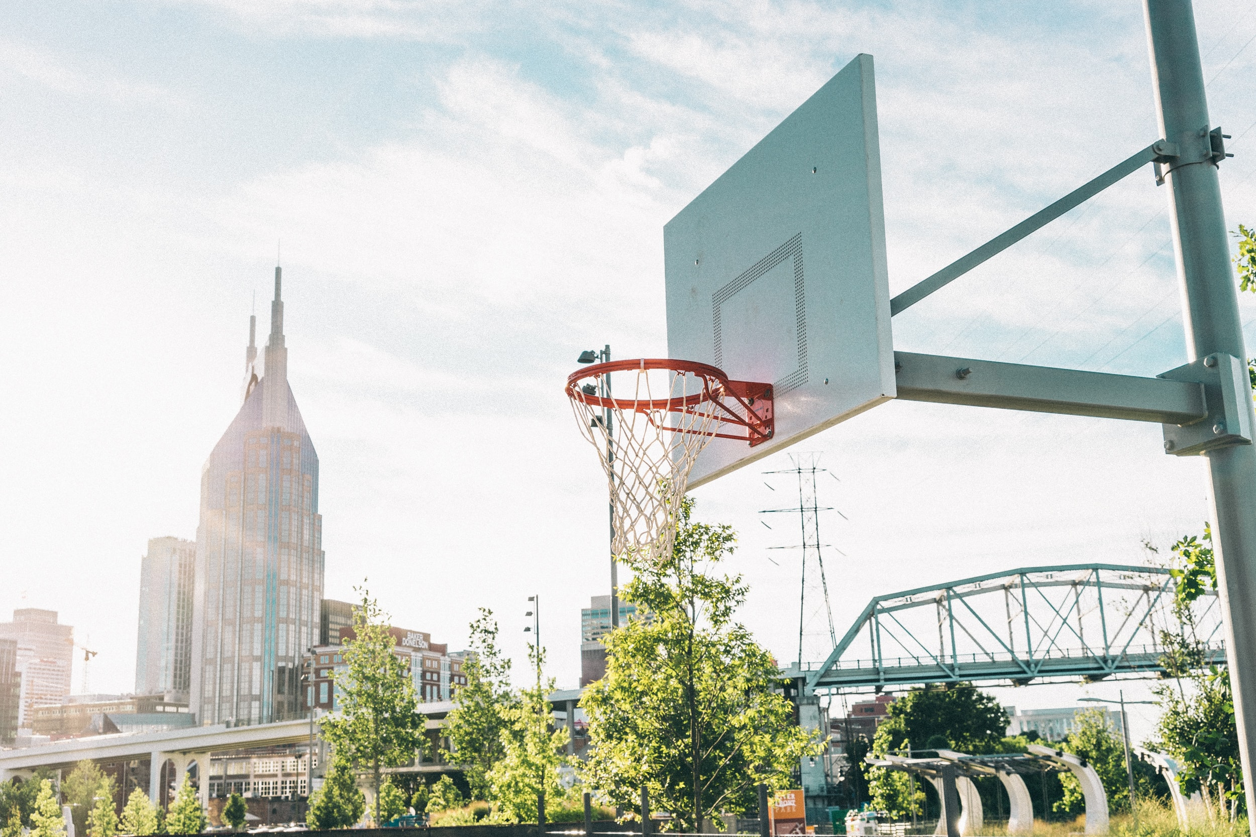 An outdoor basketball hoop with skyscrapers in the background in Nashville