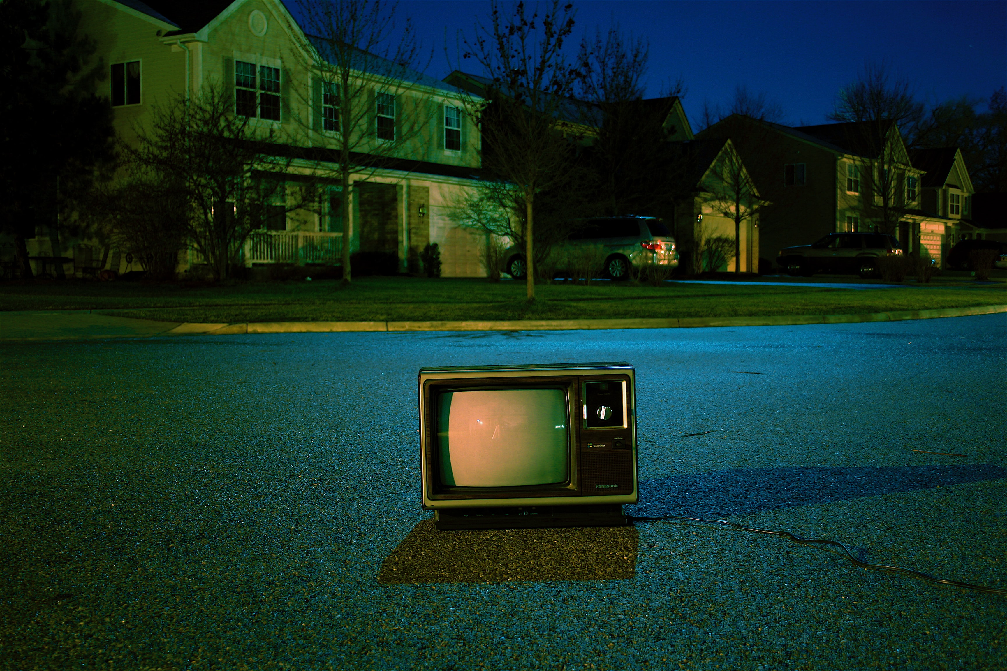 Night-time shot of retro TV in middle of neighborhood road in suburbs