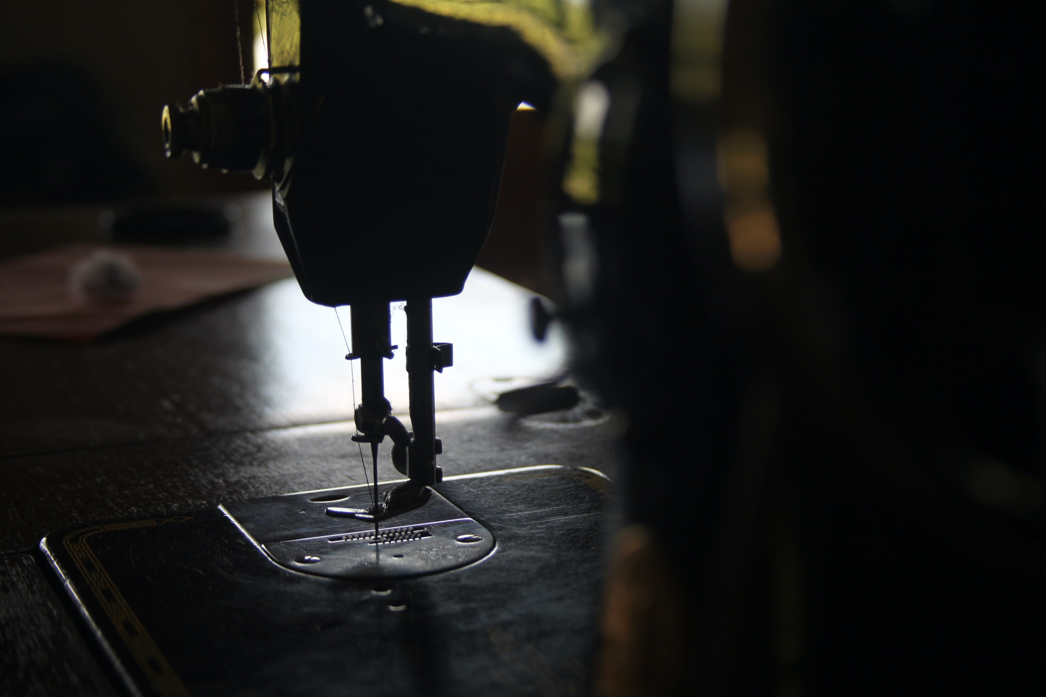 Macro of a sewing machine stitching in a dark room
