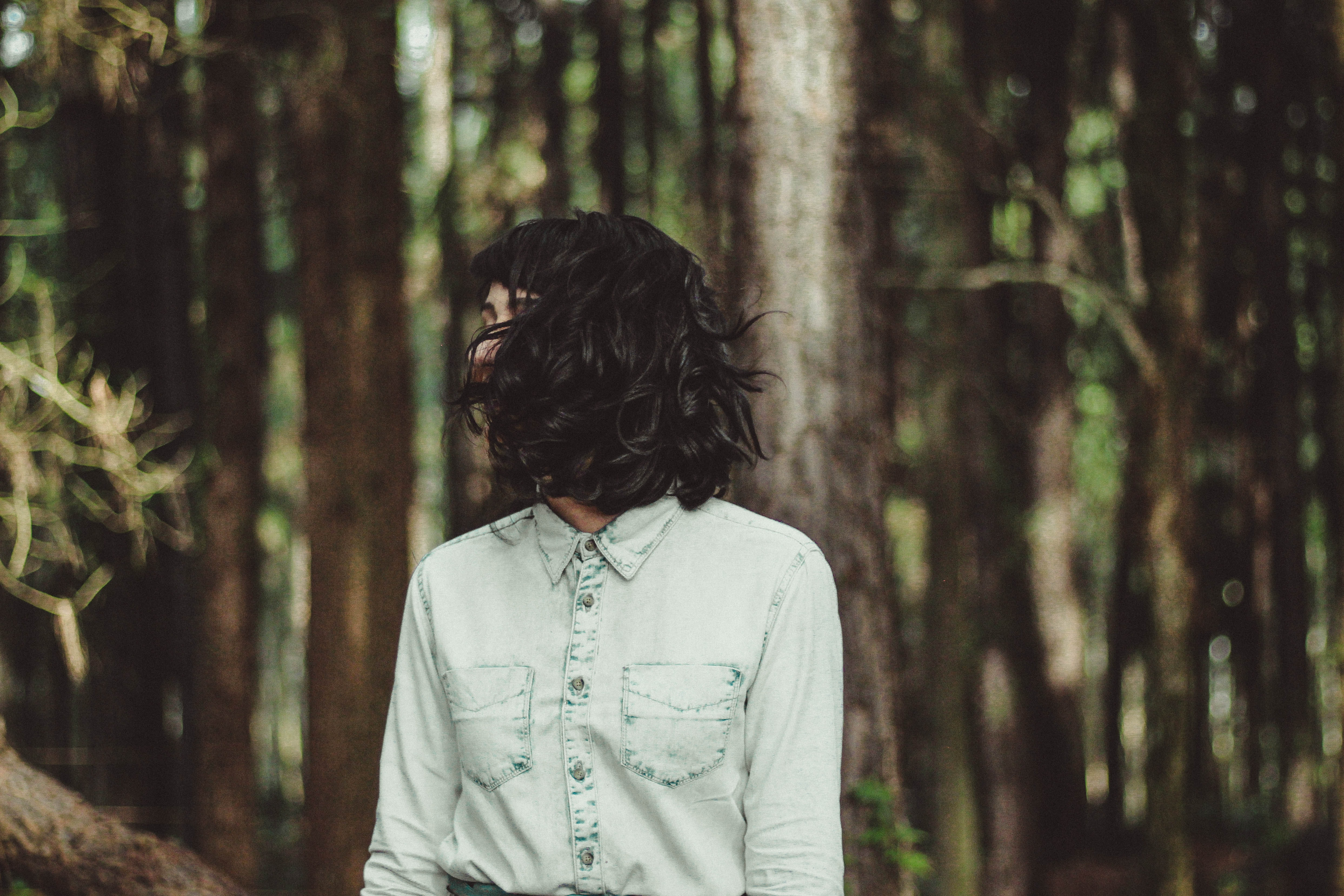 A brunette woman in a denim shirt in a forest
