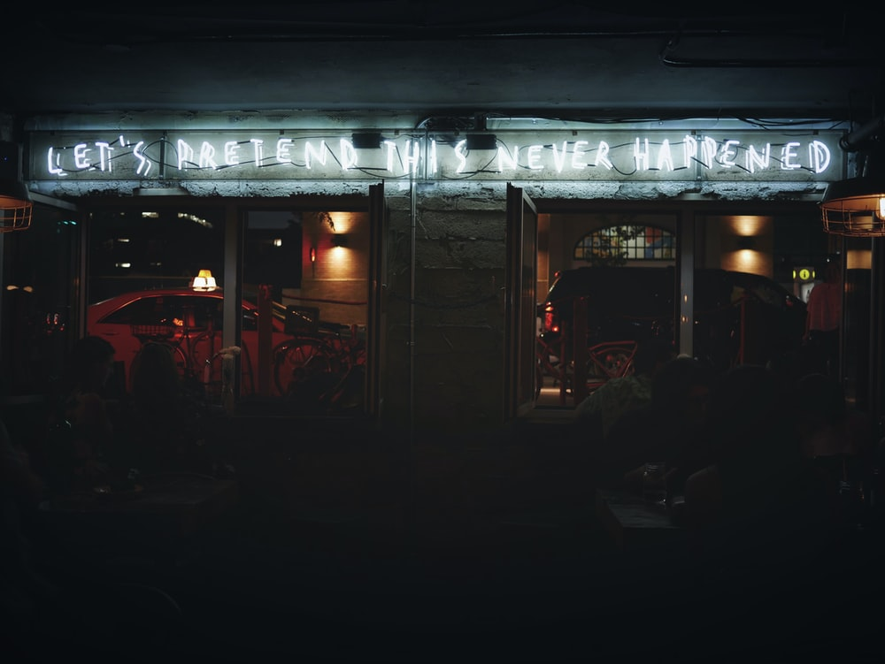 focus photo of Let's Pretend This Never Happened neon light signage