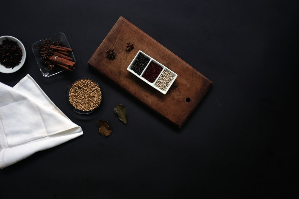 flat lay photography of beans on brown wooden board beside white handkerchief