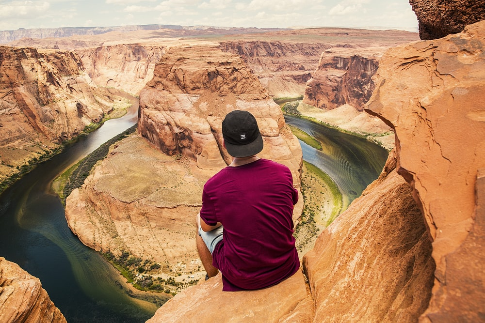 man sitting on brown mountain located at Grand Canyon during daytime