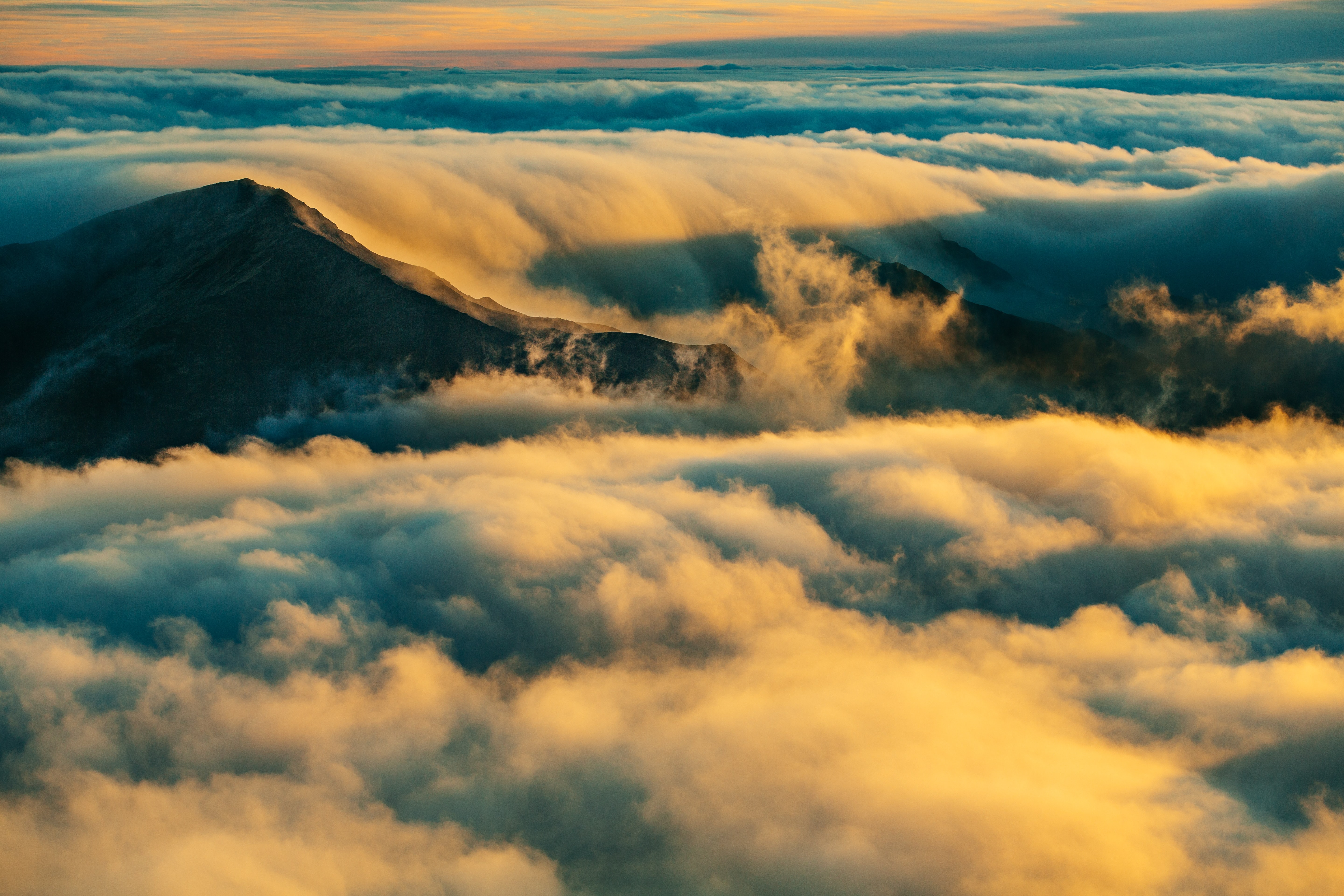 Yellow and blue clouds engulf a mountain during golden hour at Haleakala Summit Parking