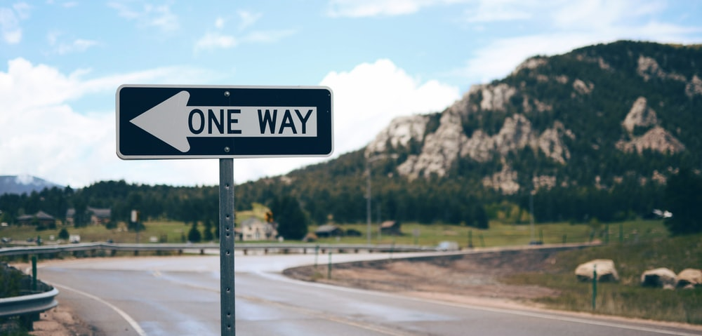 One Way street sign beside road far at the mountain during daytime