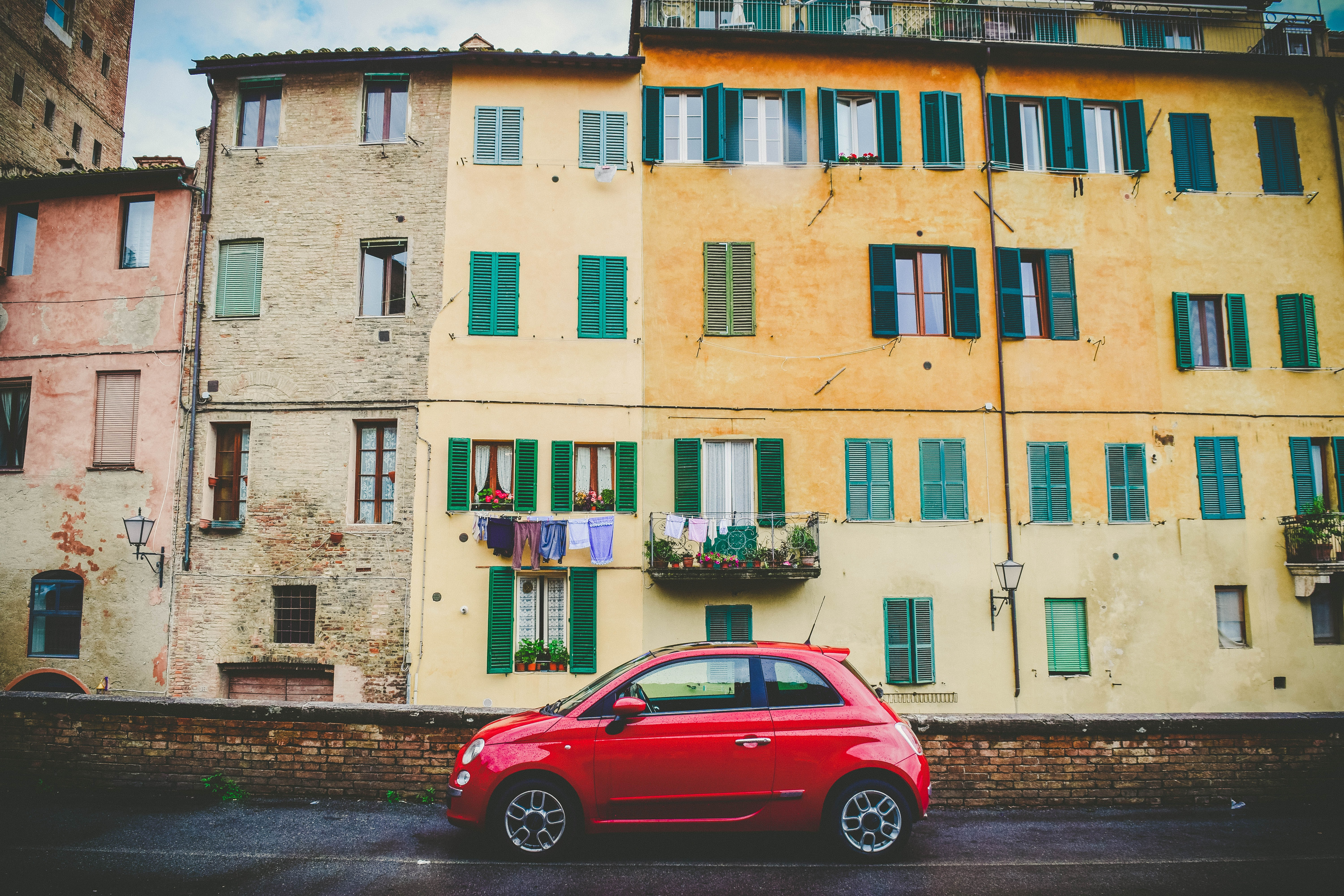 Modern red vehicle parked in front of traditional yellow apartments with green windows, Province of Siena