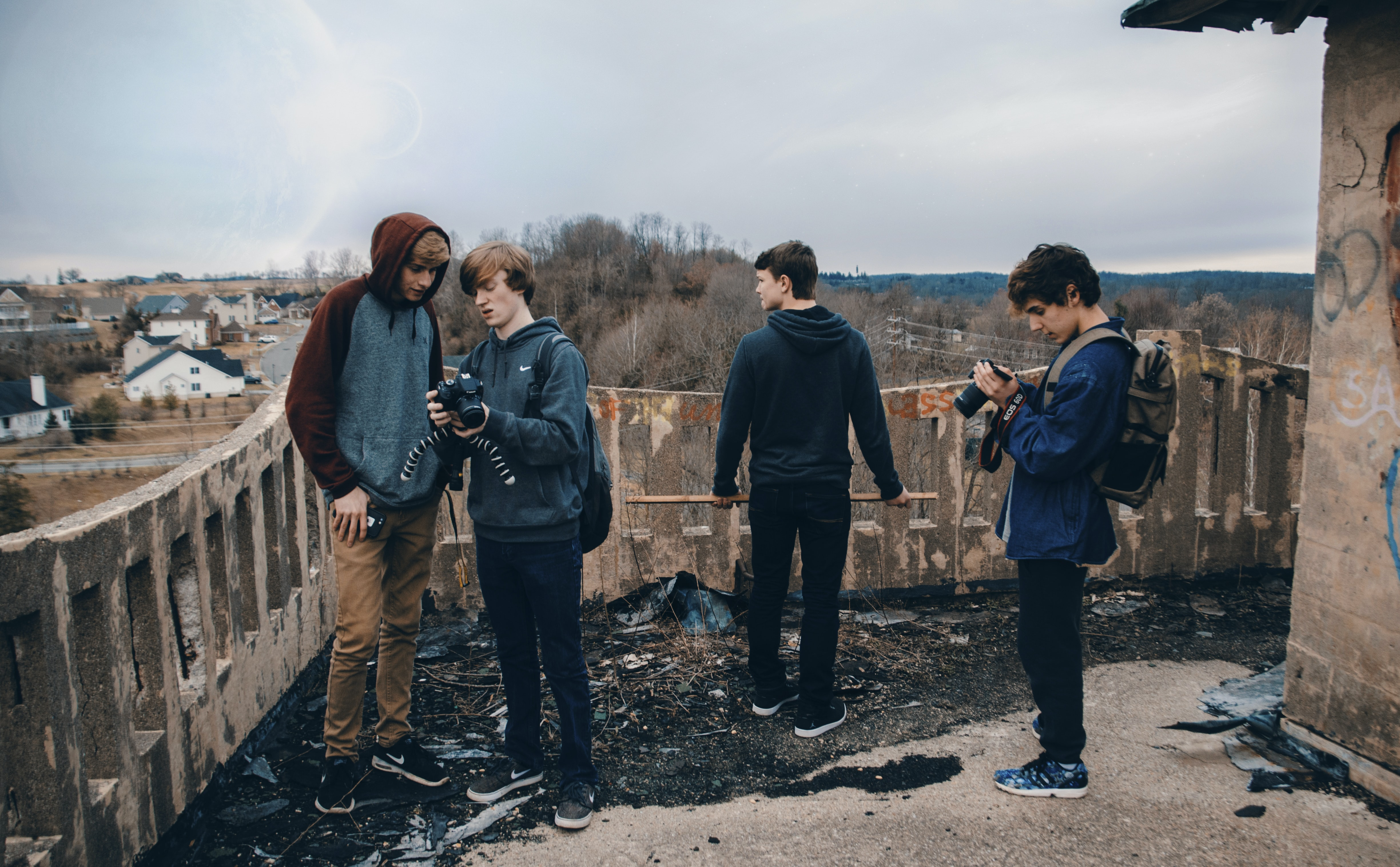 four man wearing blue jackets standing beside house looking at their cameras during daytime
