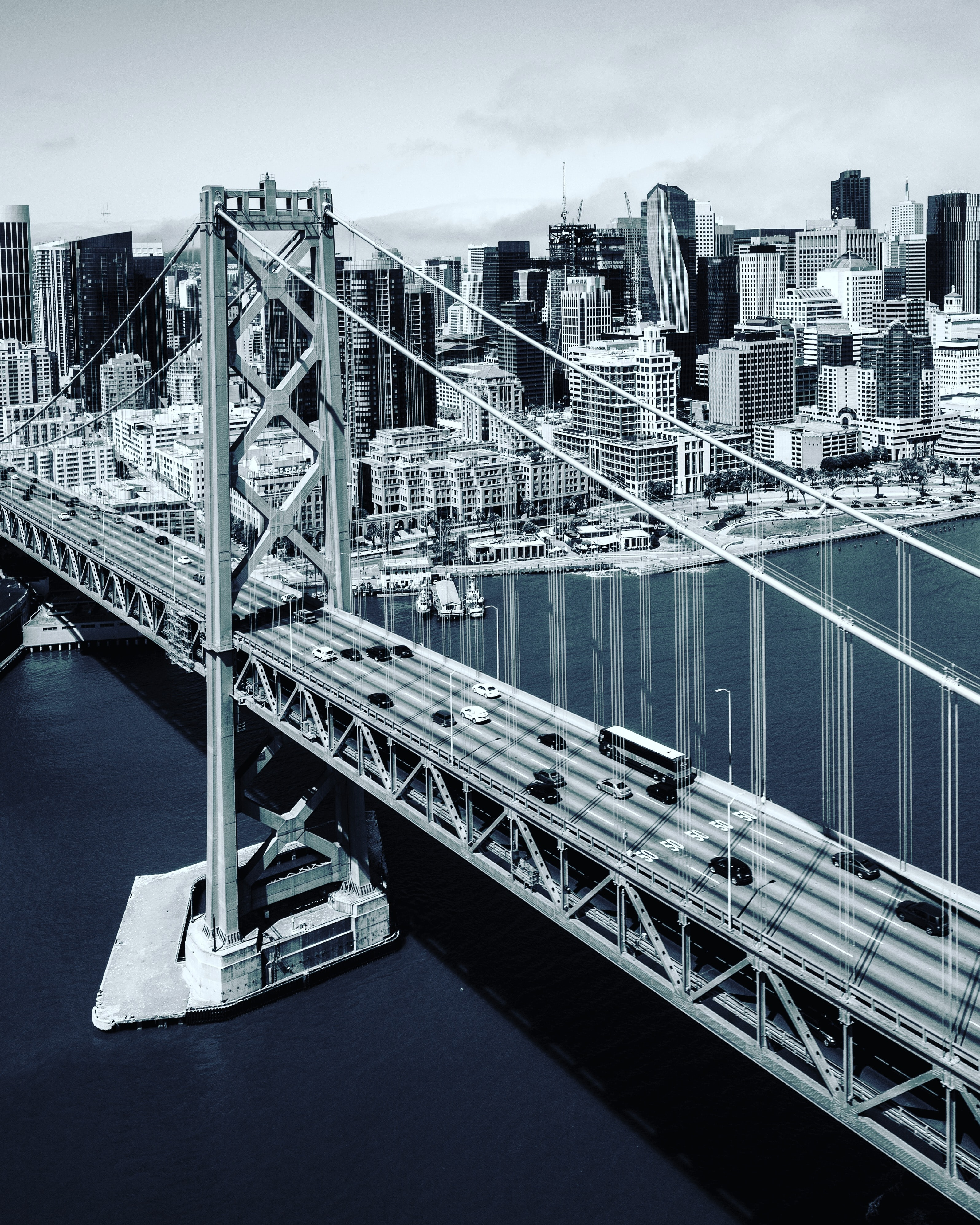 A black and white aerial shot of the bridge connecting San Francisco to Oakland