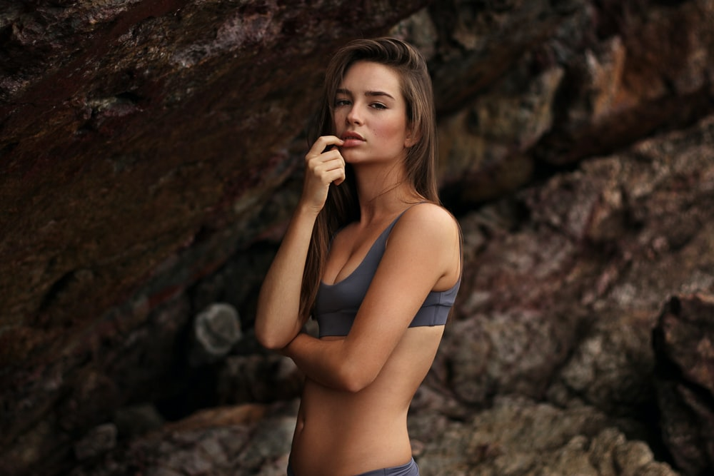 woman wearing black sport brassiere standing beside gray rock