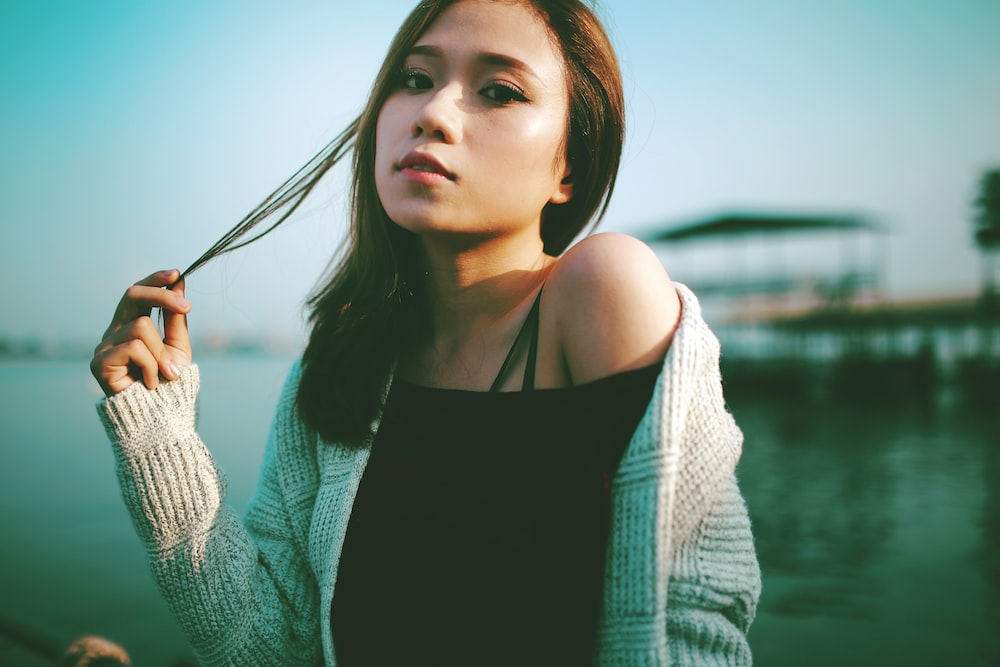 selective focus photo of woman holding string of hair near body of water during daytime