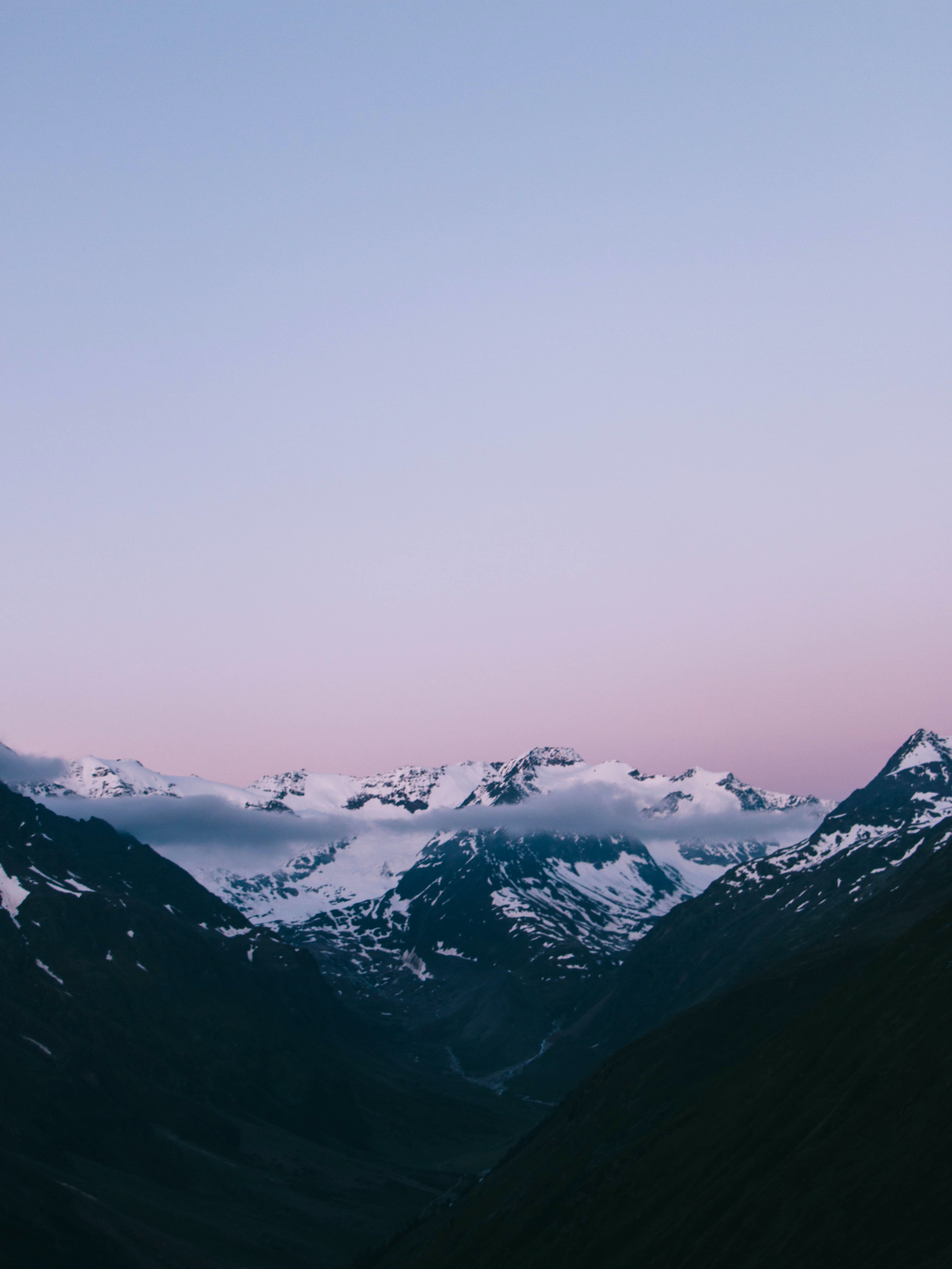 The top of snowy mountains under a light blue and violet sky