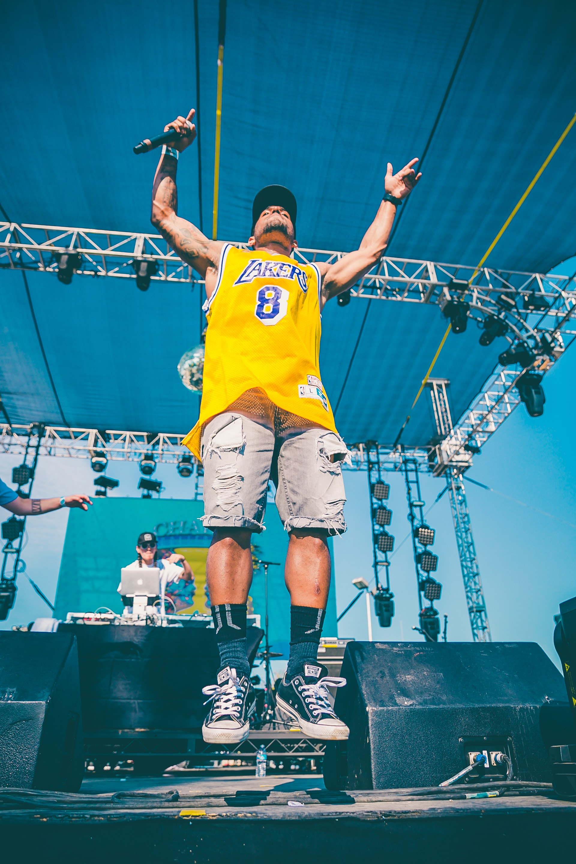 A man with a microphone in a yellow Lakers shirt jumping up on stage