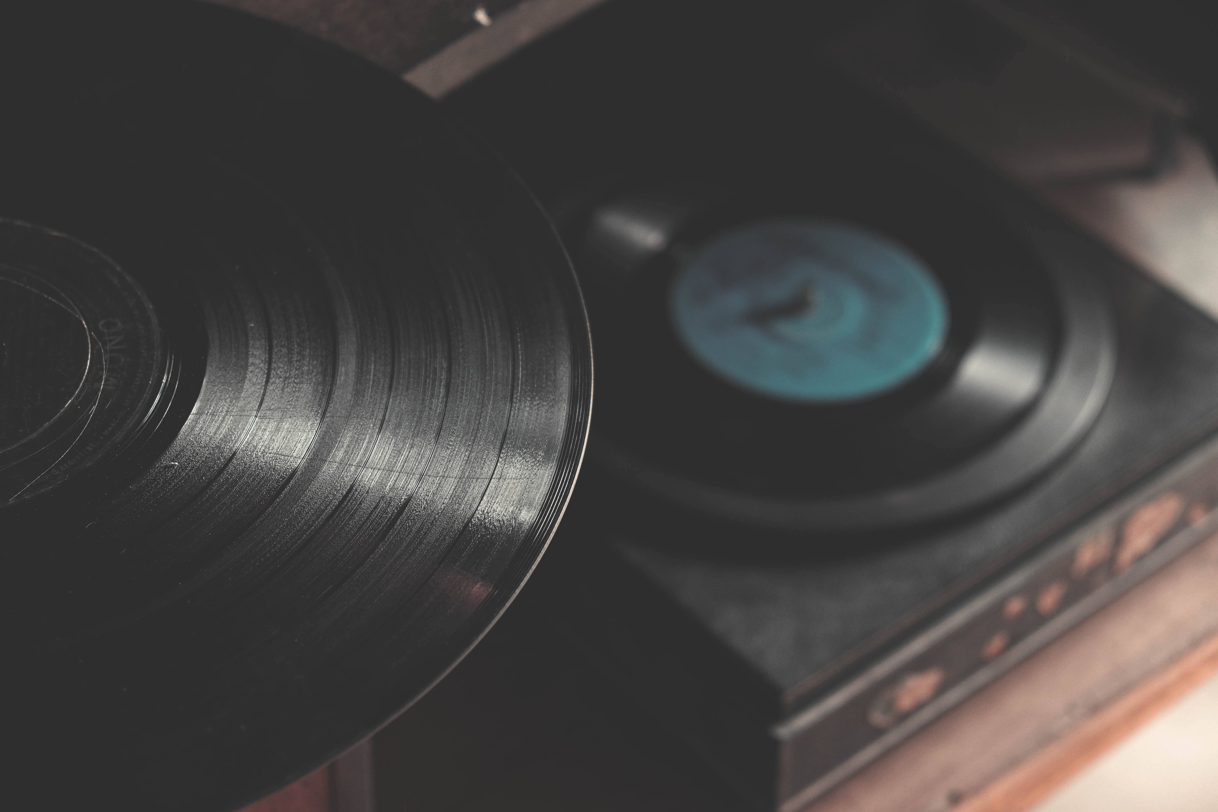 An overhead shot of a vinyl record on a cabinet over a vinyl player