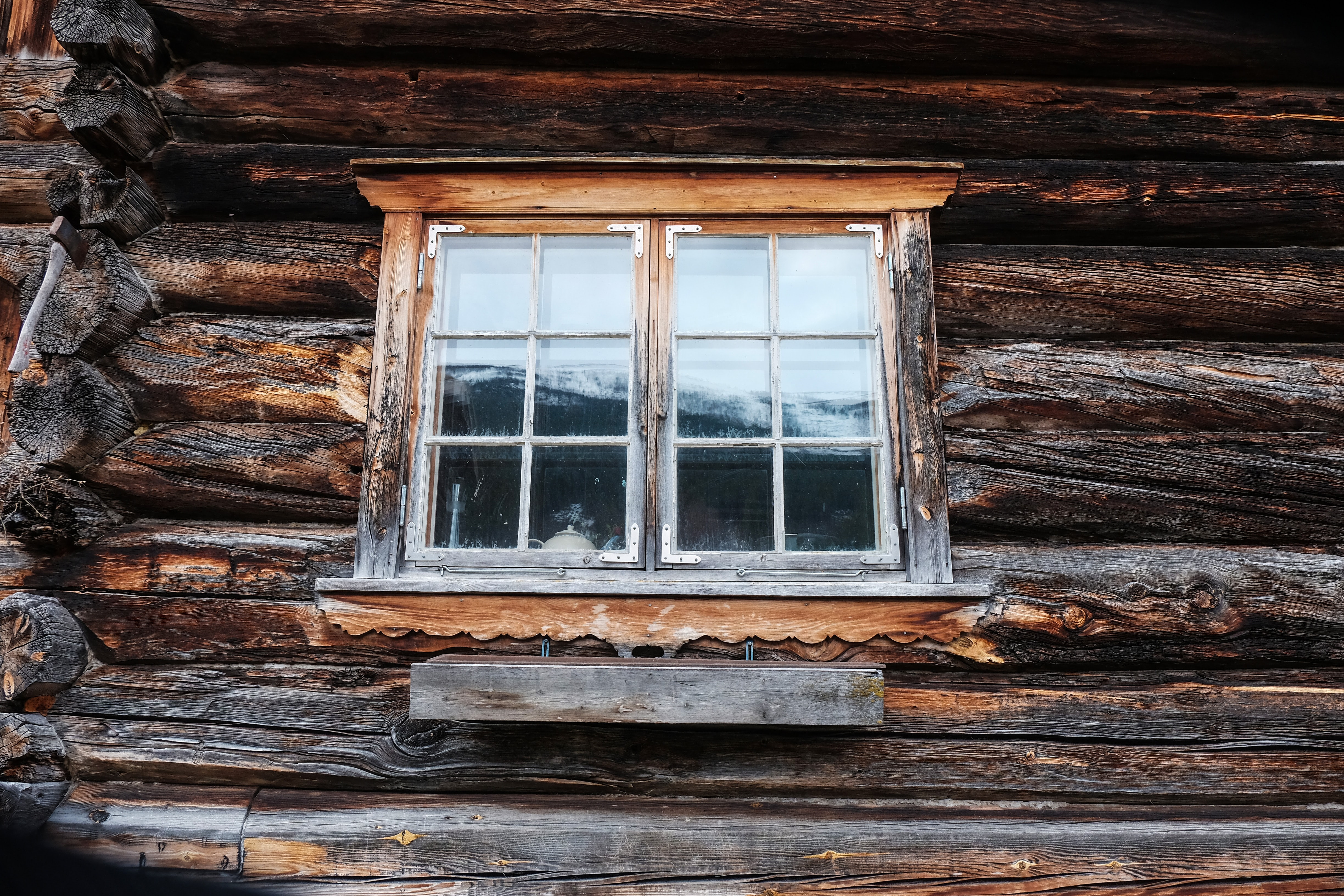 Window on the exposed timber of a log cabin with white capped mountains in the background
