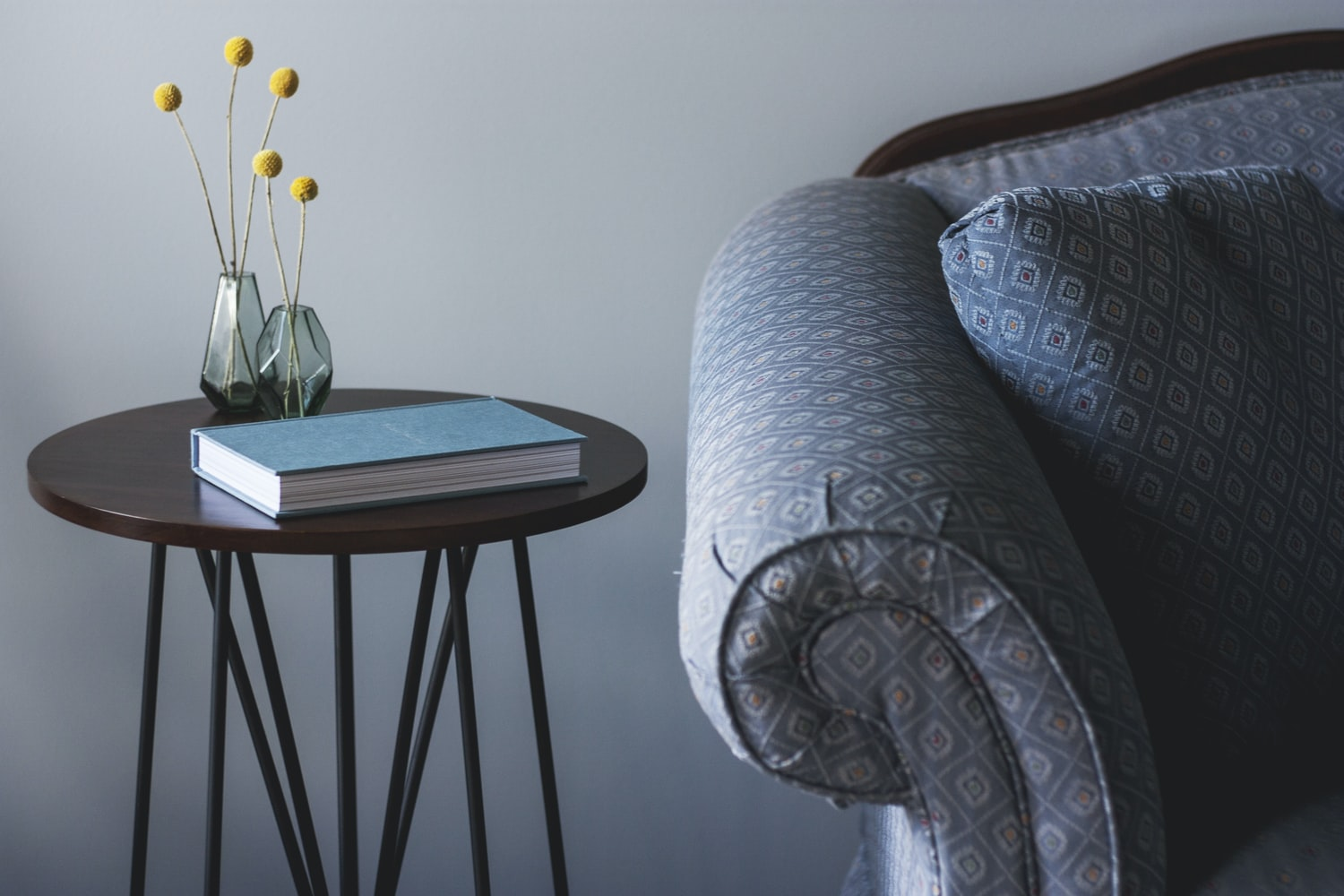 table with book and flower vase beside couch