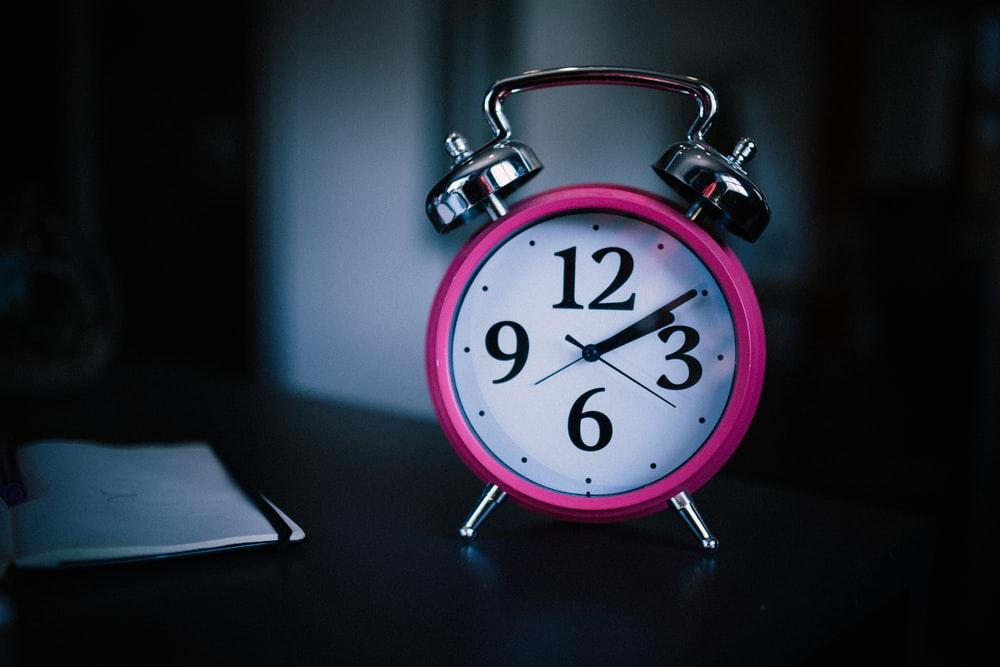 pink bell alarm clock showing 2:10