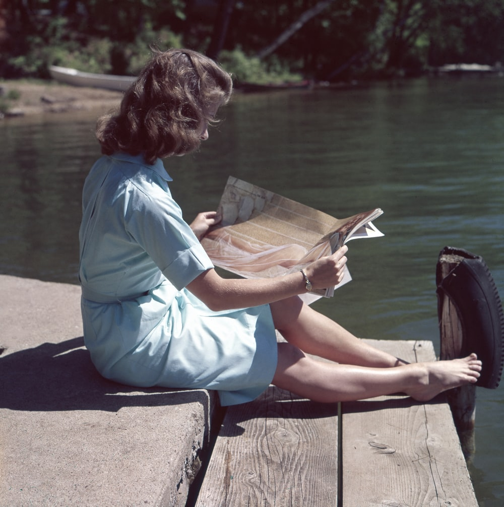 woman wearing blue dress reading magazine near body of water during daytime