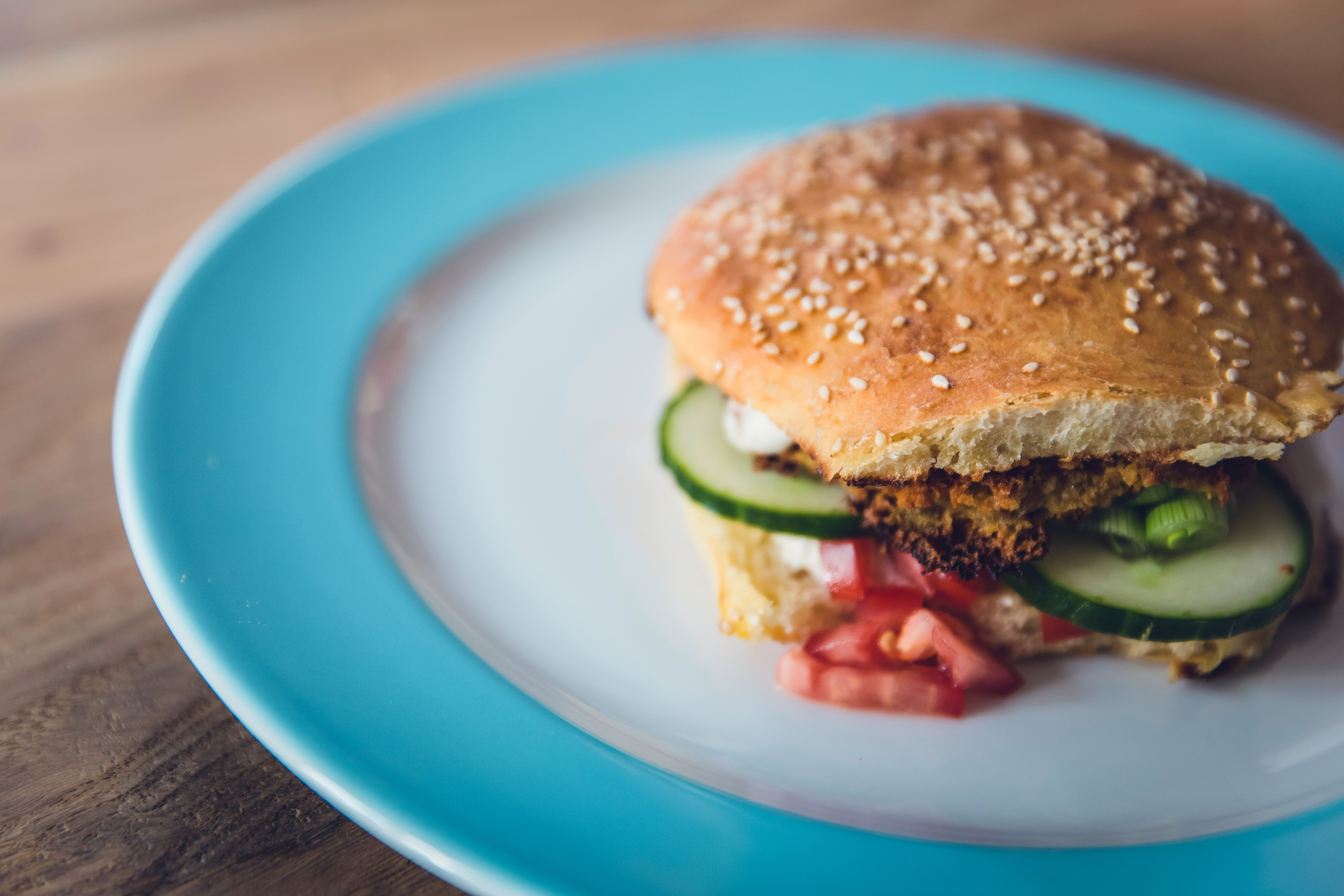 Vegetarian burger on hamburger bun with cucumbers and tomatoes on blue and white plate