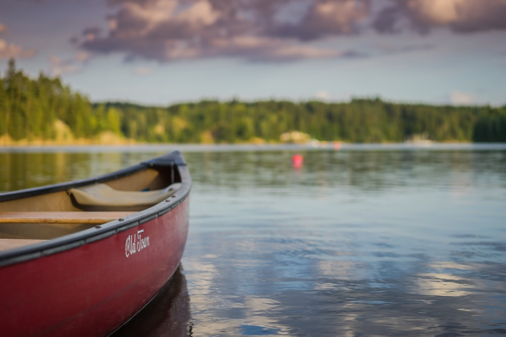 red canoe boat on body of water