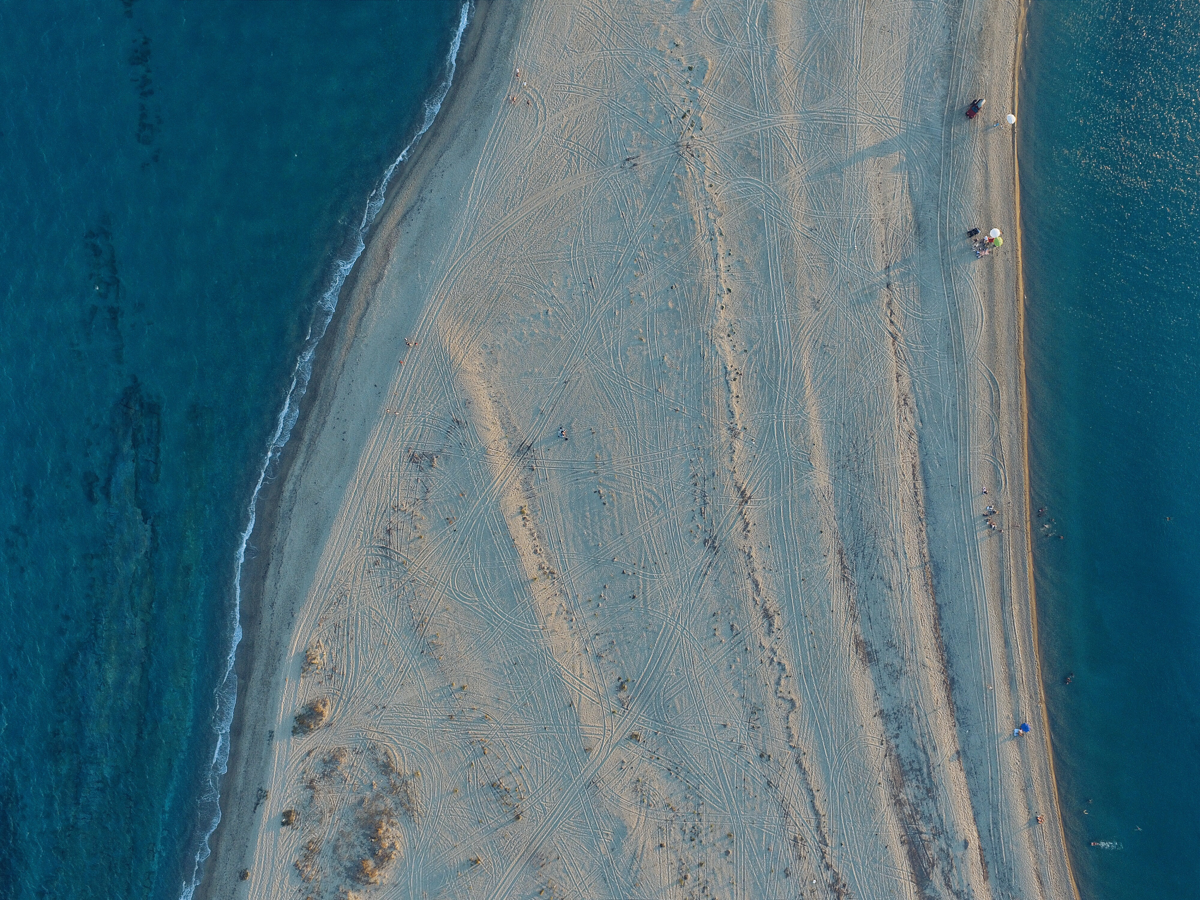 aerial view of white sand surrounded by body of water