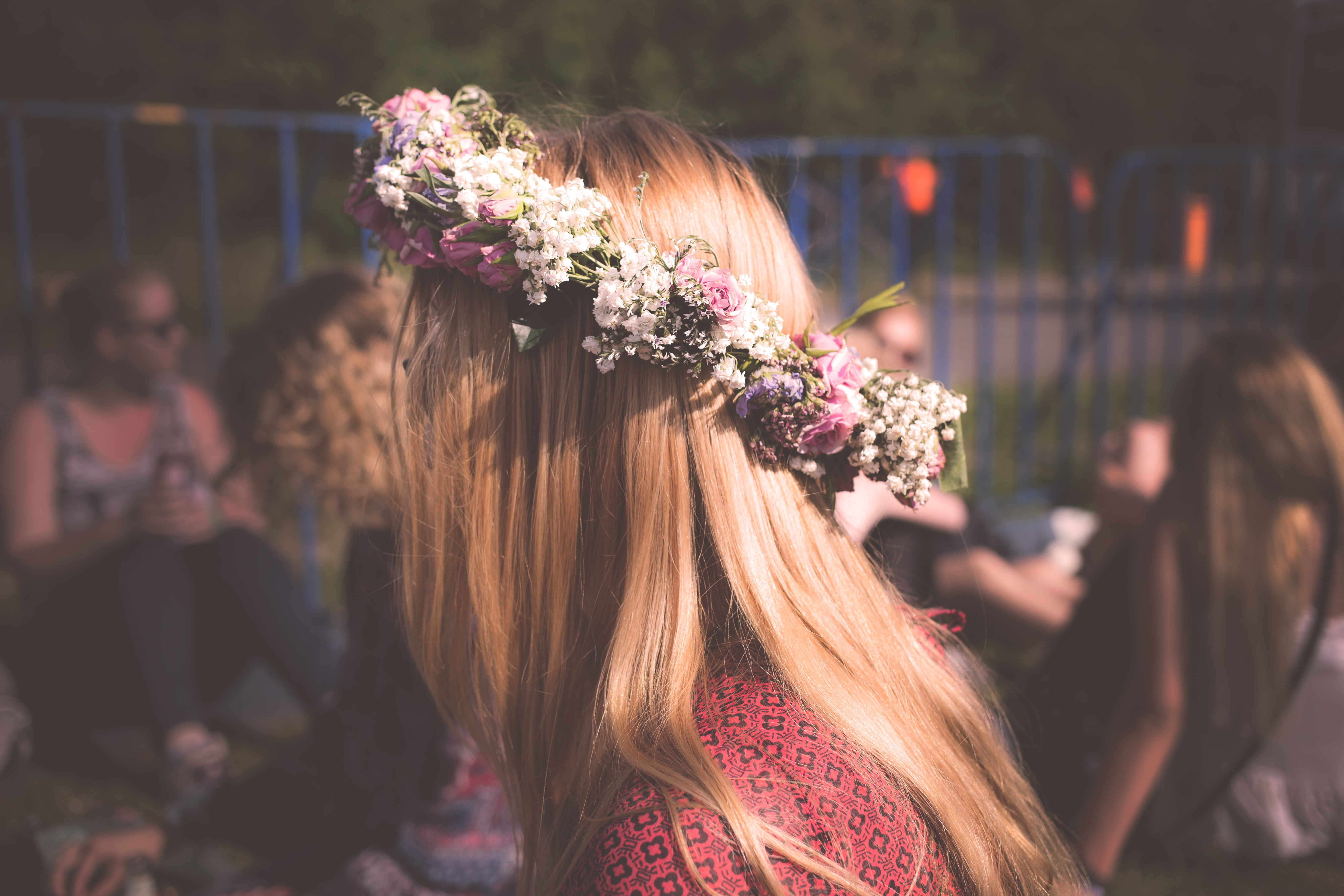 A blonde woman in a headband made of tiny multi-colored flowers