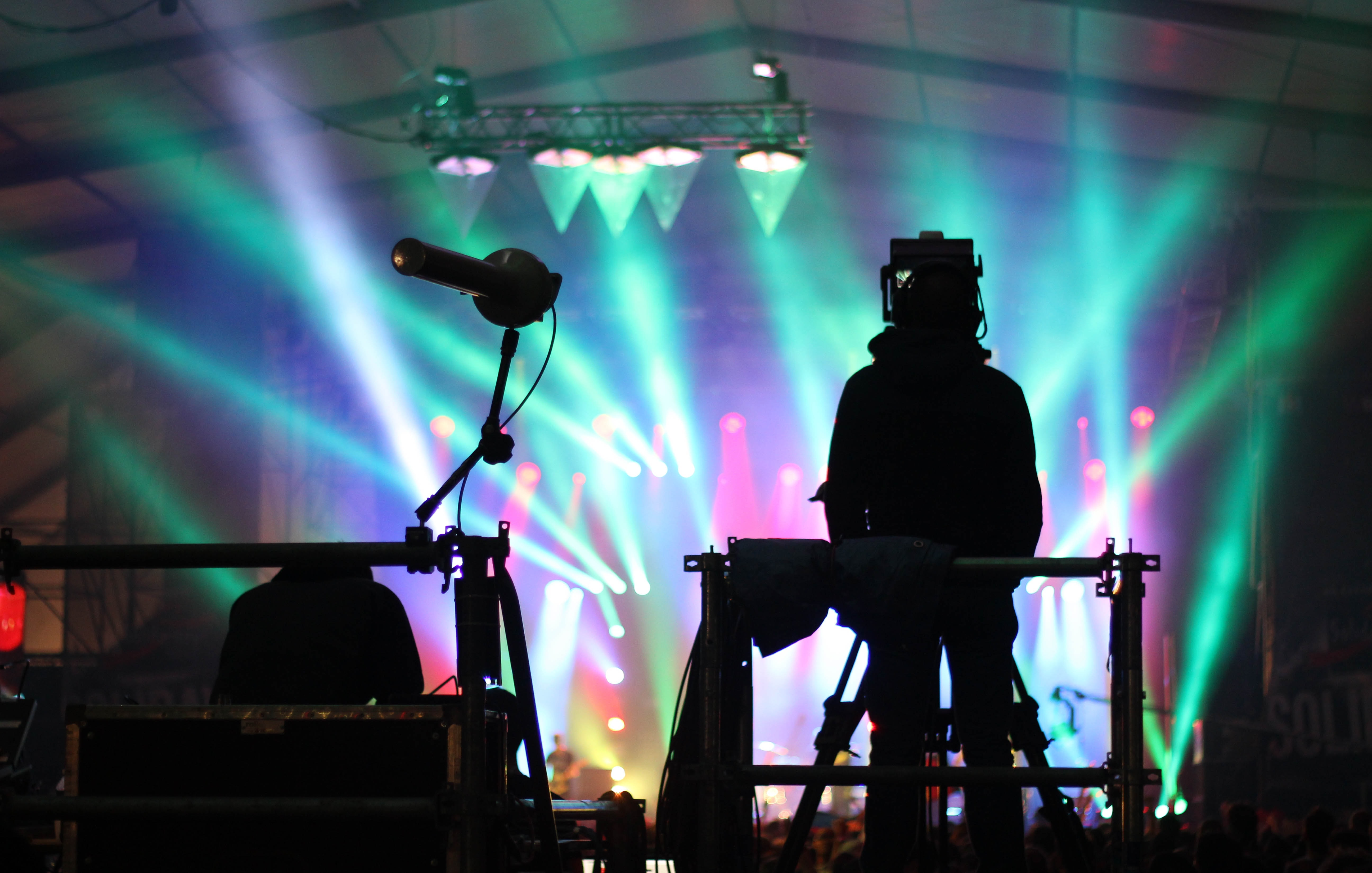 A silhouette of a technician at the back of a concert venue against colorful spotlights on the stage