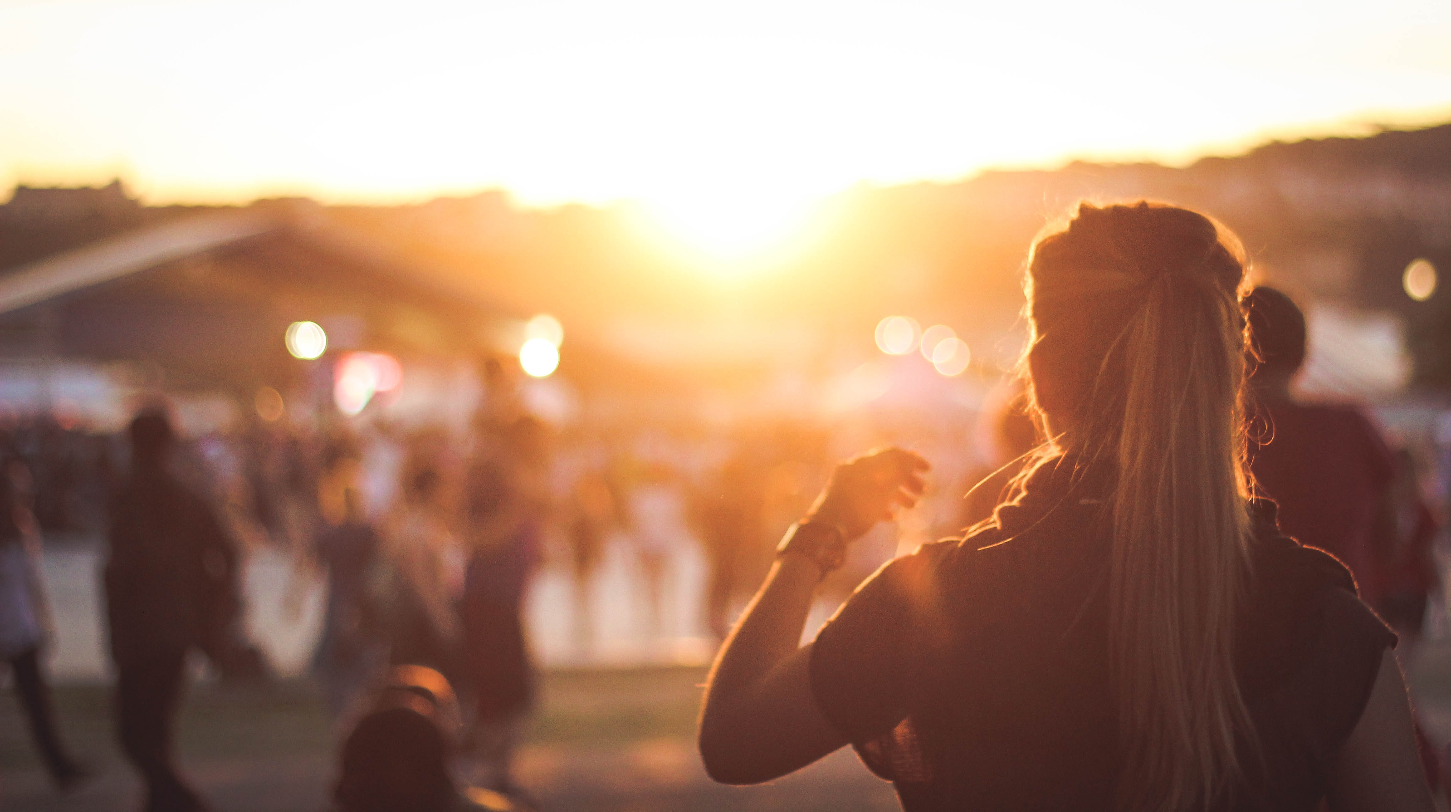 Image of a blonde woman standing in a festival with lens flares in silhouette