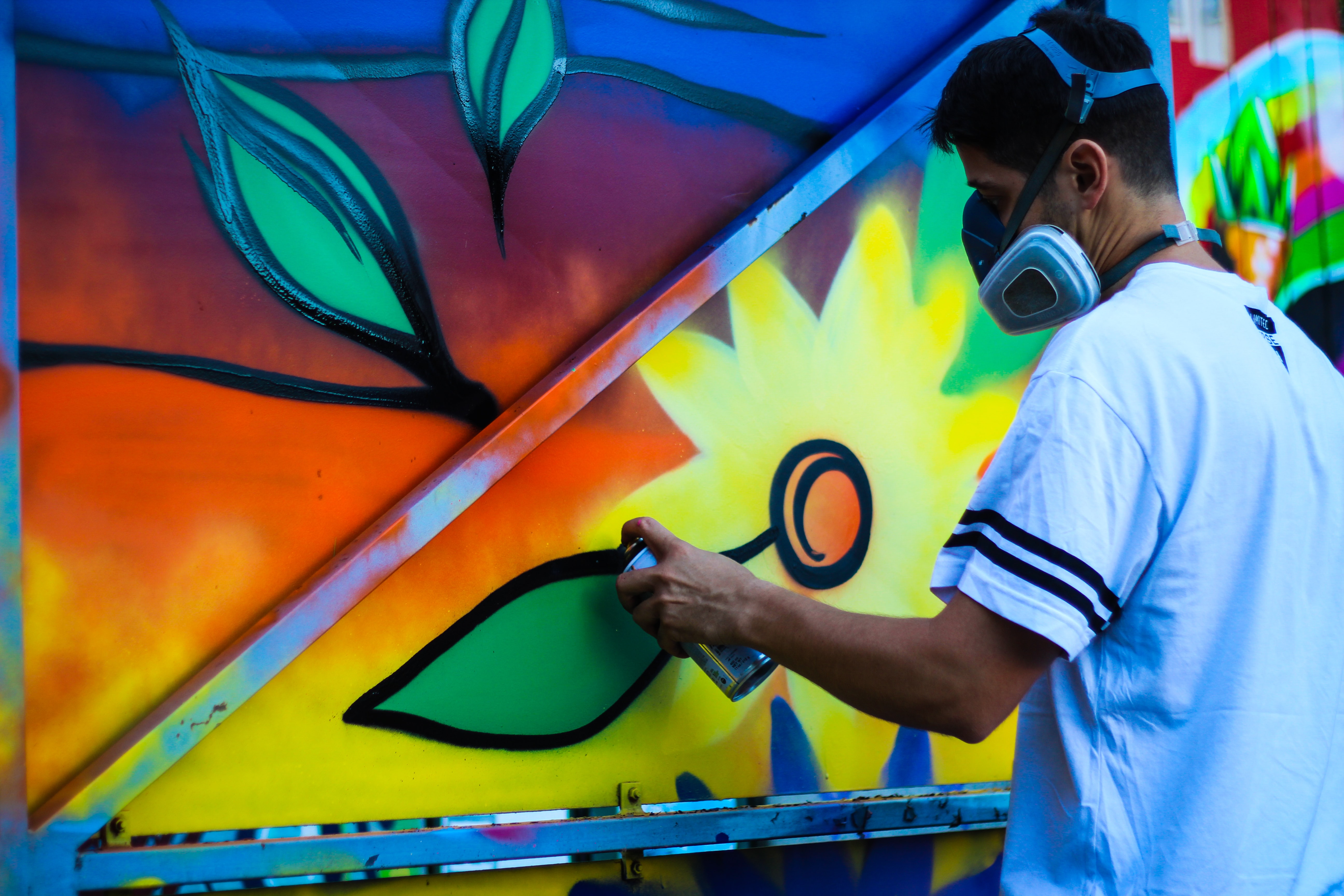 Spray paint graffiti artist in t shirt with mask holding canister creating colorful wall mural