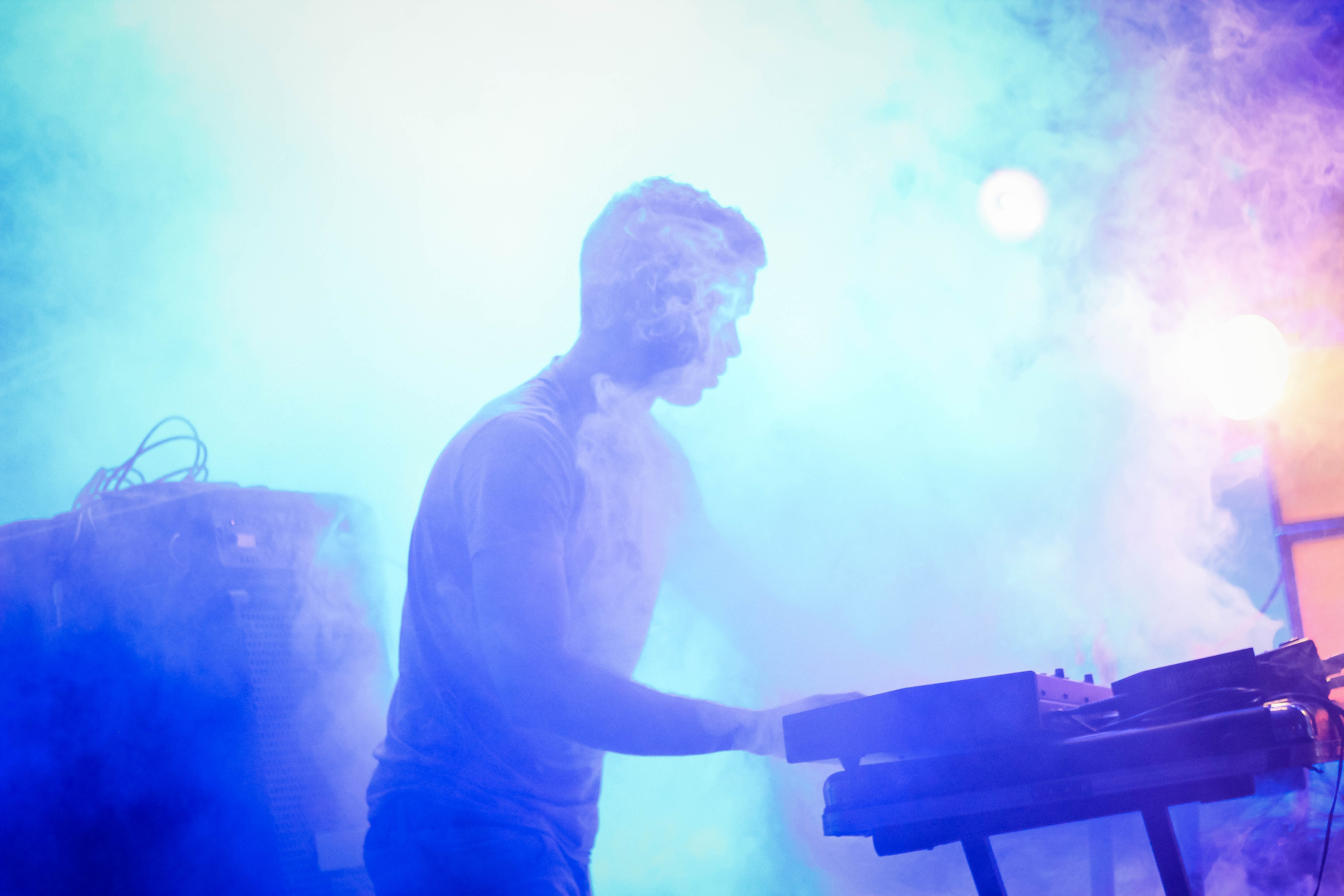 A man performing on a fog covered stage.