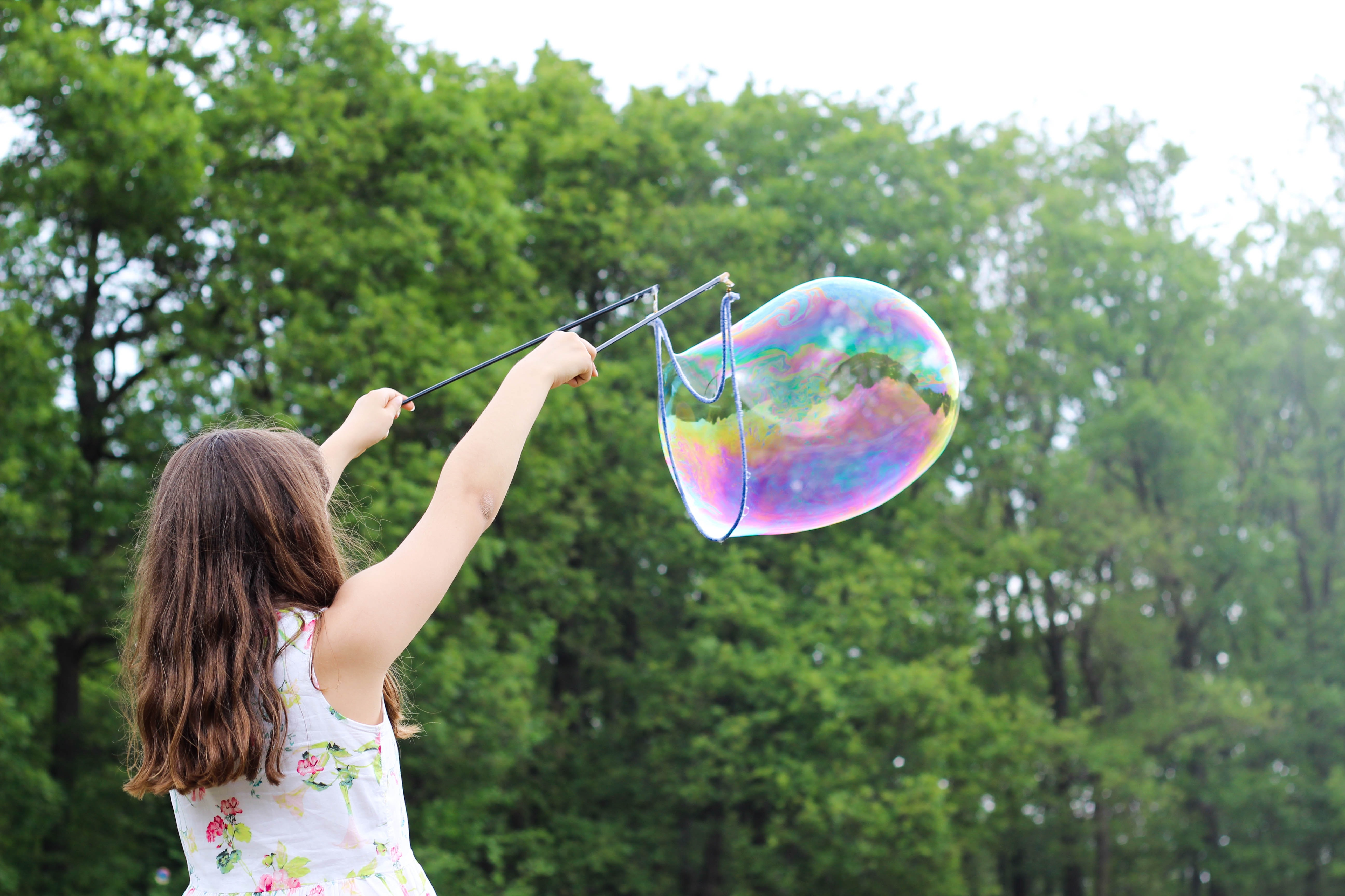 Female child using a large bubble wand to form a big soap bubble in the air