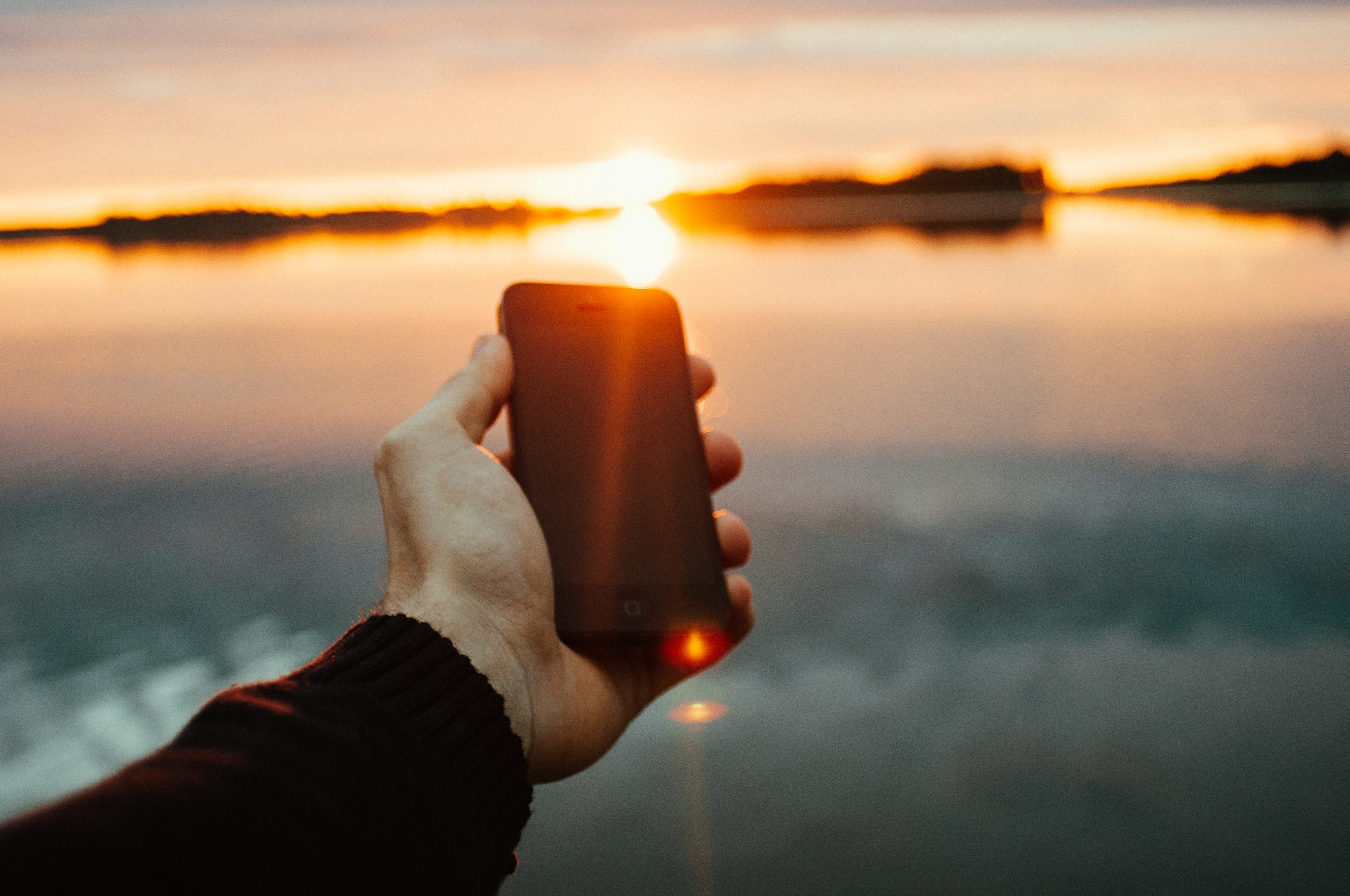 A person's hand holding a smartphone over a body of water at sunset