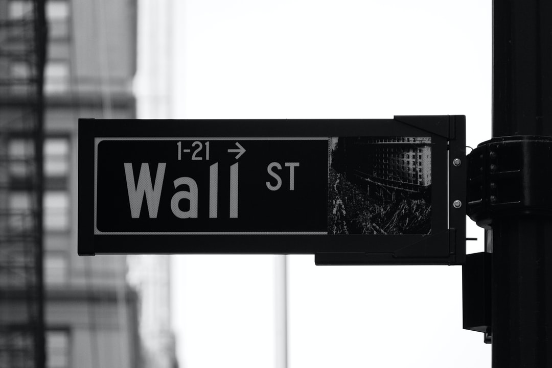 Black and white photo of the street sign for Wall St in New York City